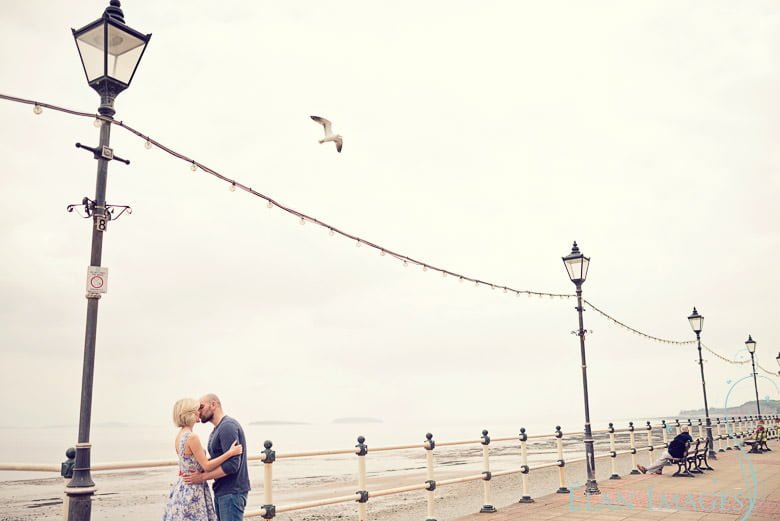 A lone seagul flying over the couple during their engagement photo shoot in Cardiff