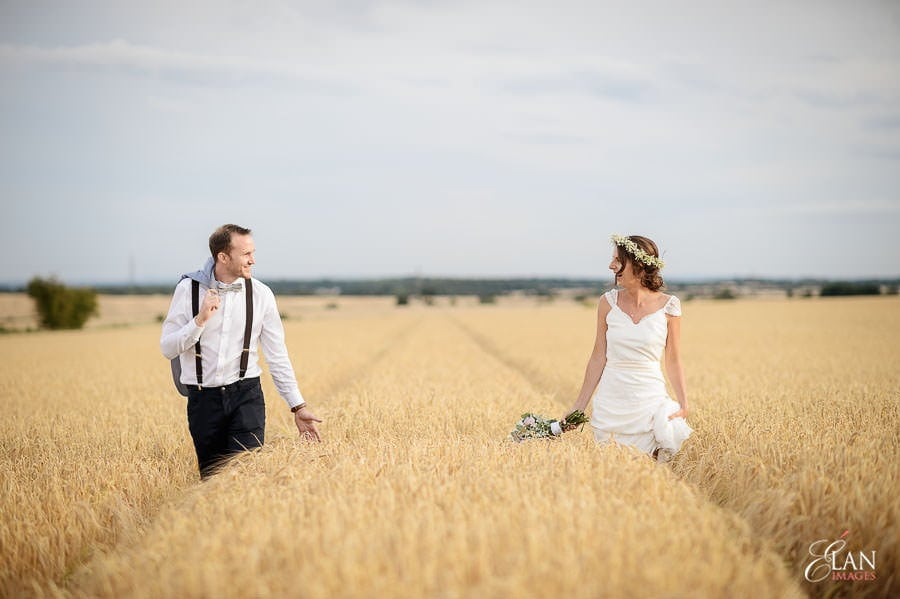Bride and Groom photographed walking in the corn fields after their wedding at Stone Barn