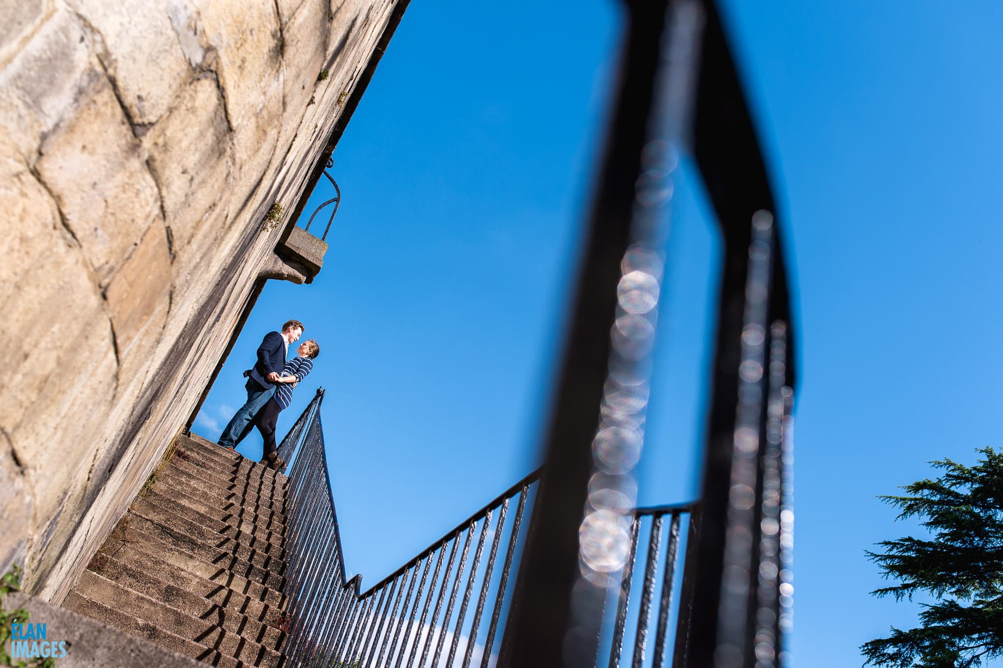 Bristol Engagement Photographer - couple kissing with a deep blue sky in Clifton Village