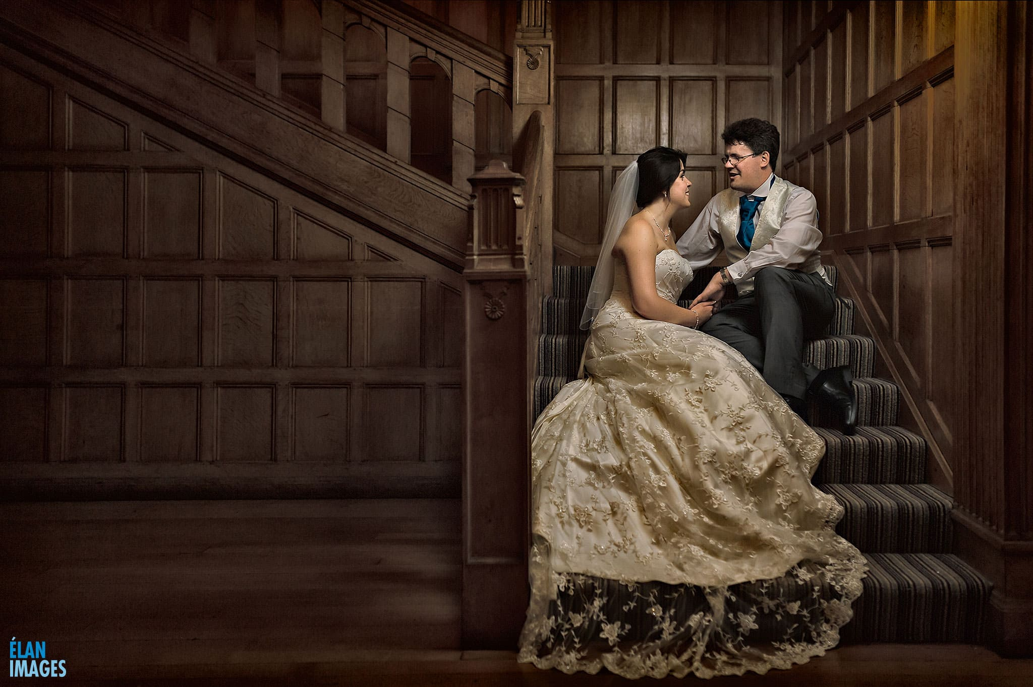Bride and groom sitting on the stairs at their wedding in Coombe Lodge in Blagdon. Lit by off camera flash.