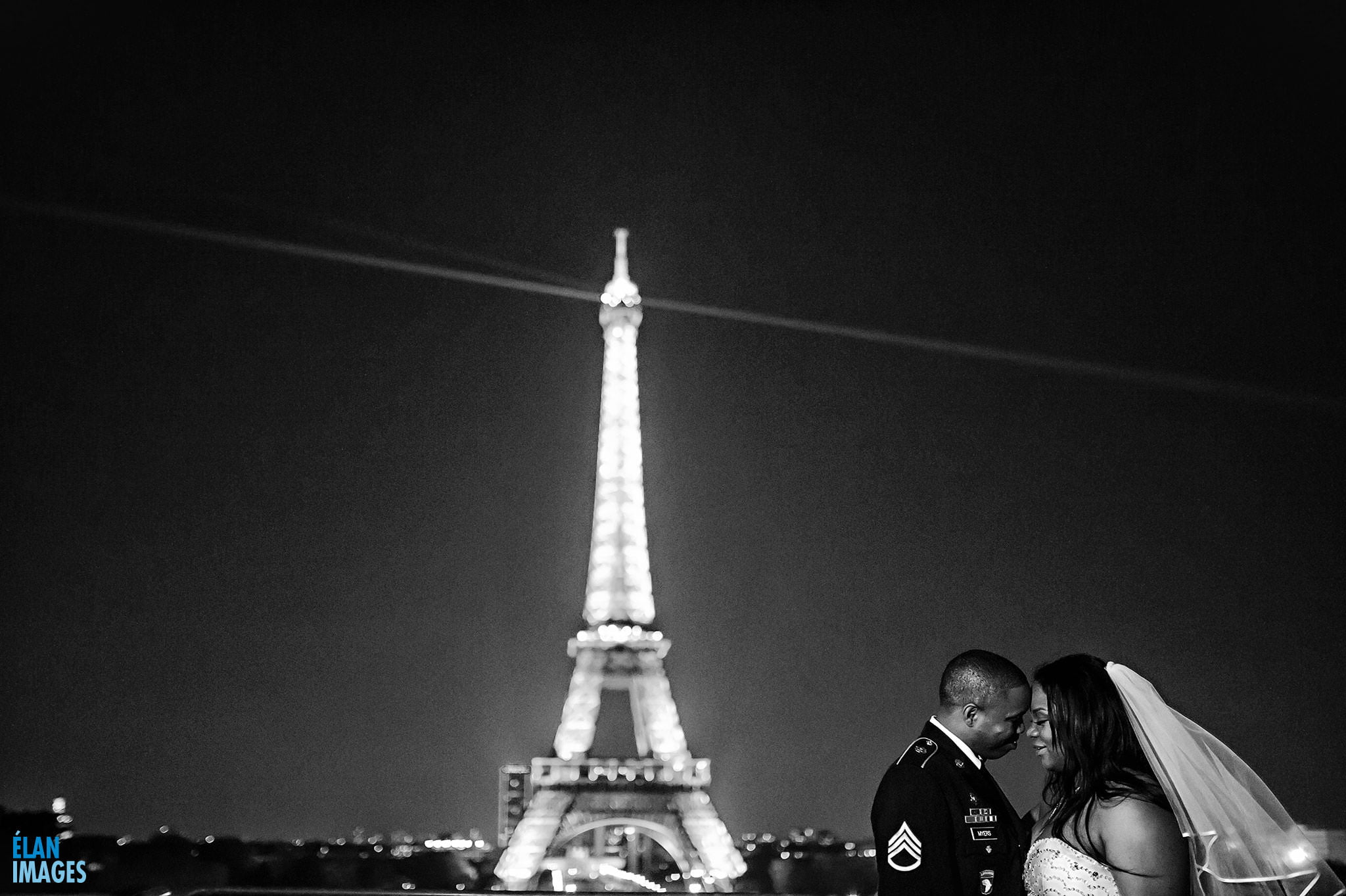 The end of a long day - the bride and groom relax and enjoy the evening light show on the Eiffel Tower, after getting married at the American Church in Paris, France.