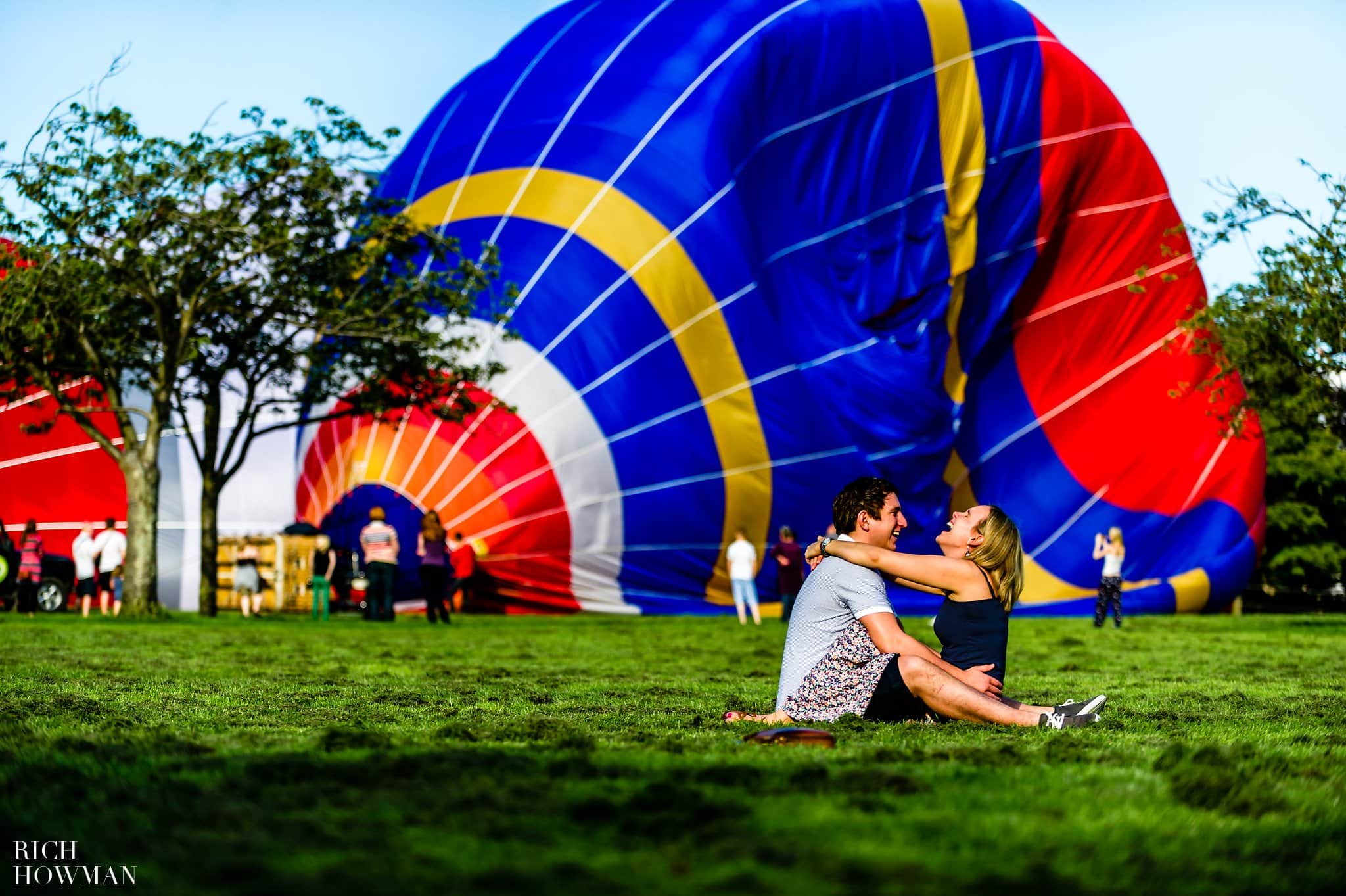 Hot air balloons take off in Royal Victoria Park in Bath whilst an engaged couple sit on the ground laughing during their engagement photo shoot in Bath, Somerset