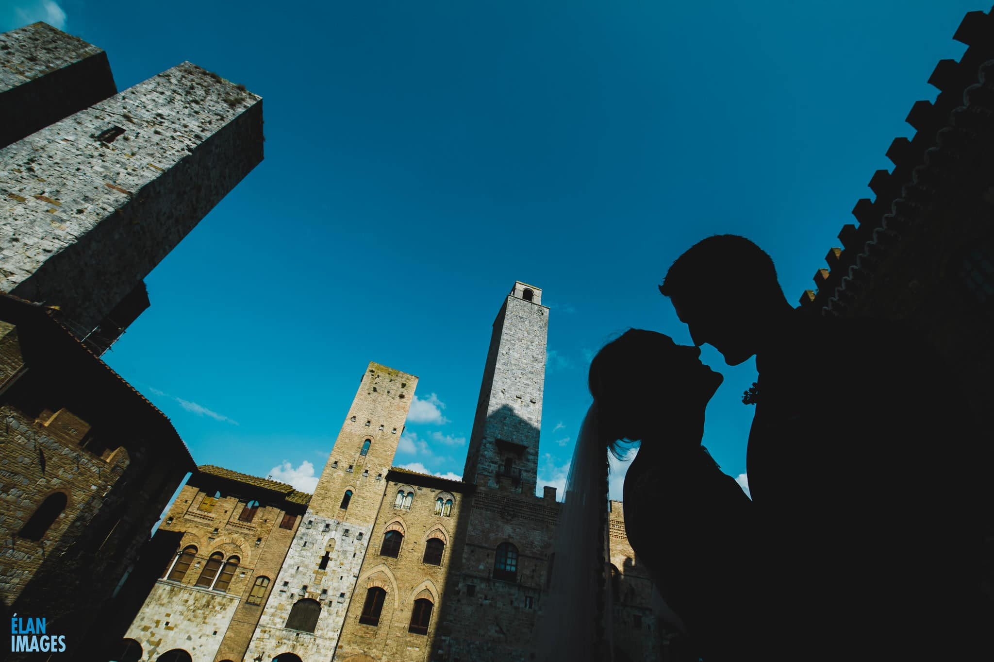 Bride and groom photographed in the midday sun just after their wedding at San Gimignano in Italy