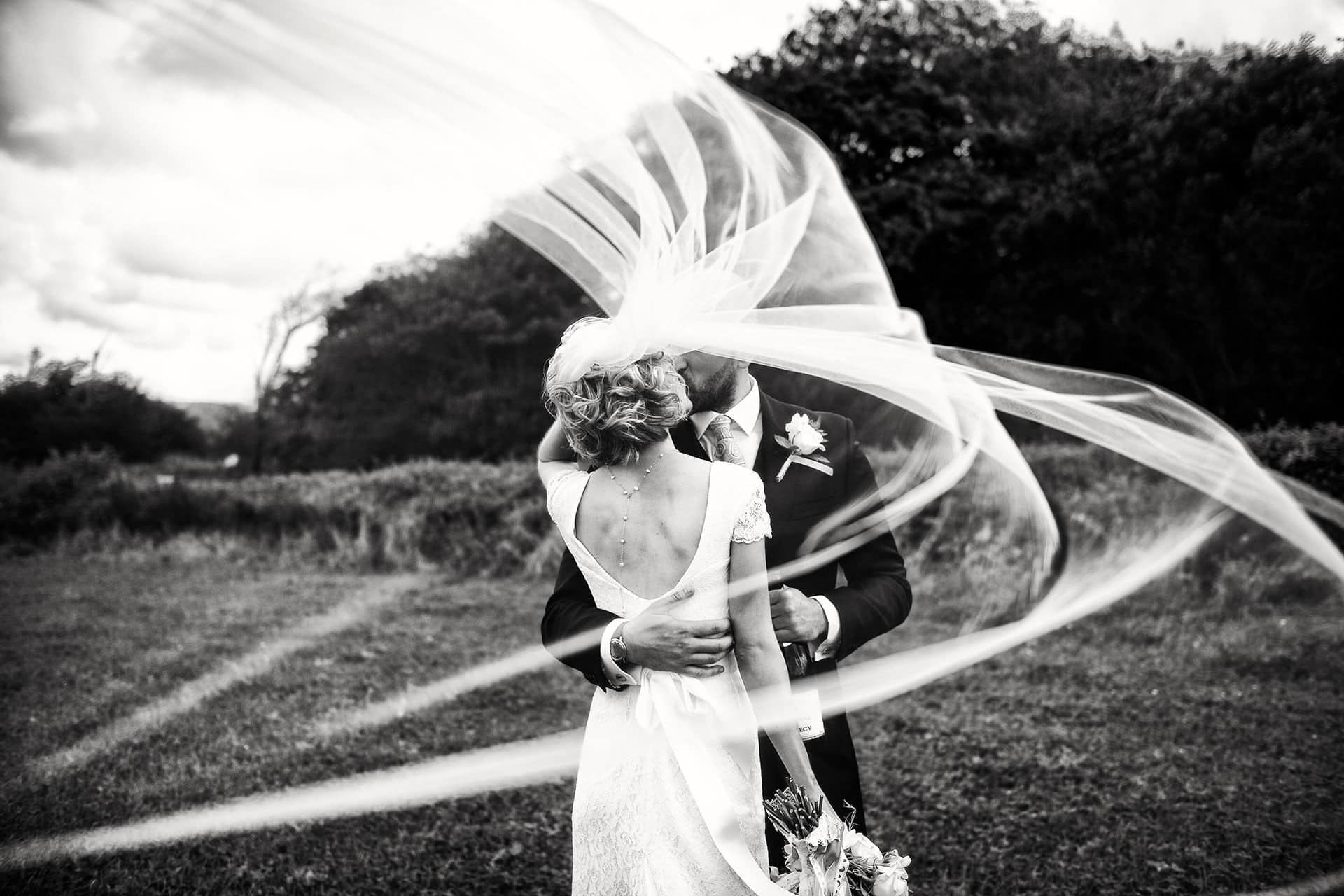 Aberaeron Wedding Photographer in West Wales. Black and white image of the Bride and groom photographed behind a veil swirling in the wind. This photo won an international ISPWP award in the movement and motion section.