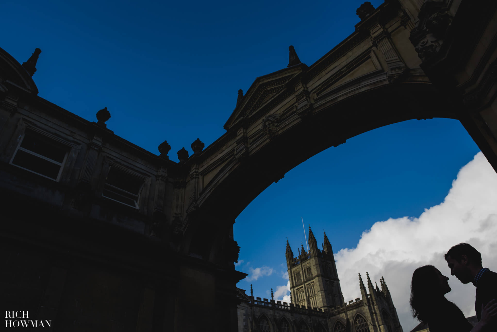 Couple silhouetted under the bridge of seize in Bath, with Bath Abbey in the background. Engagement Photography in Bath Spa