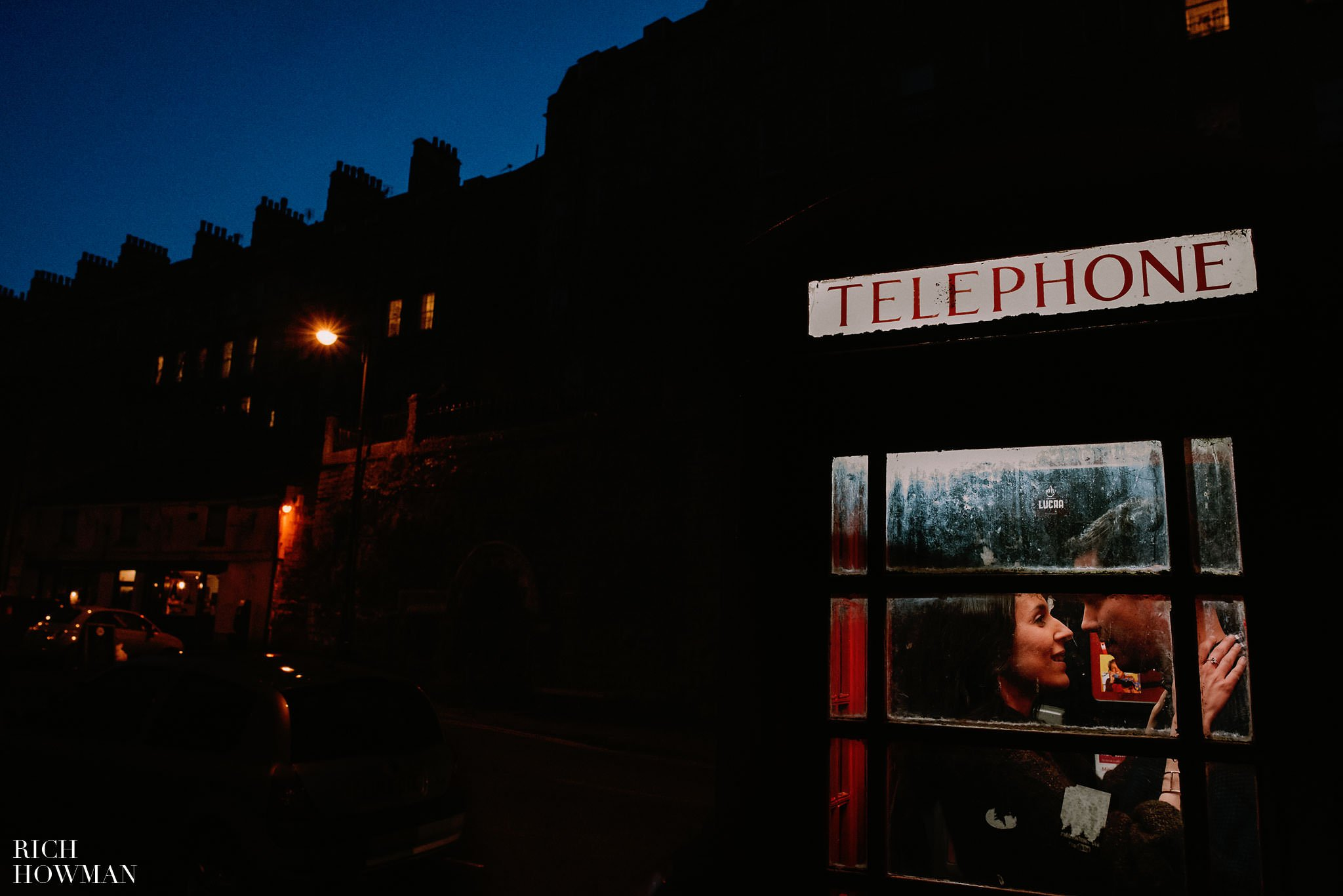 engagement photo shoot, engaged couple enjoying a moment in an old red phone box in the City of Bath in Somerset
