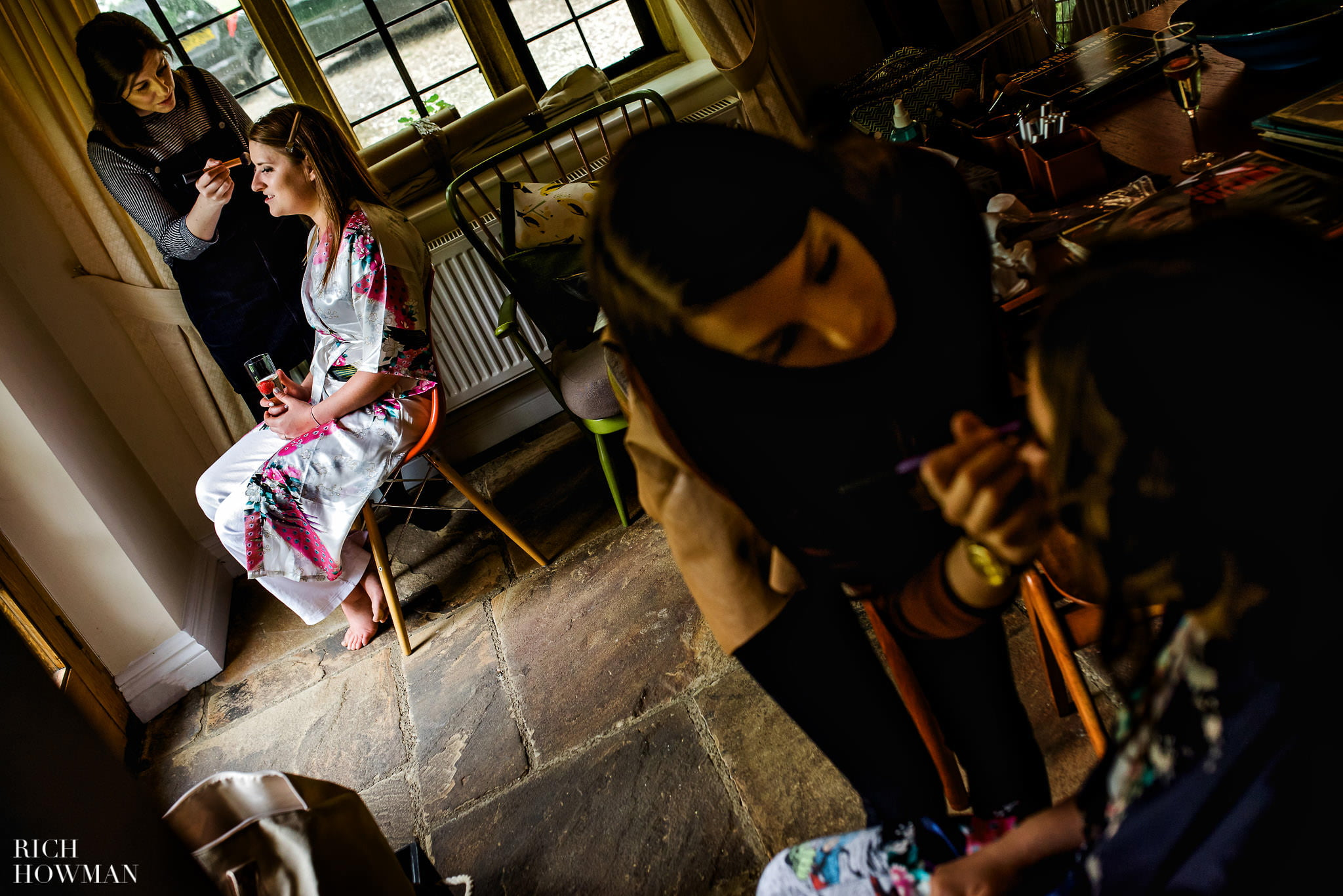 Photo of the Bride and bridesmaids having their make up done before her wedding