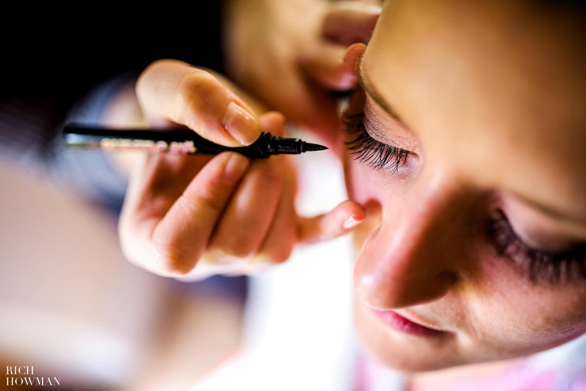 Bridal make up artist applying eye liner with a pen