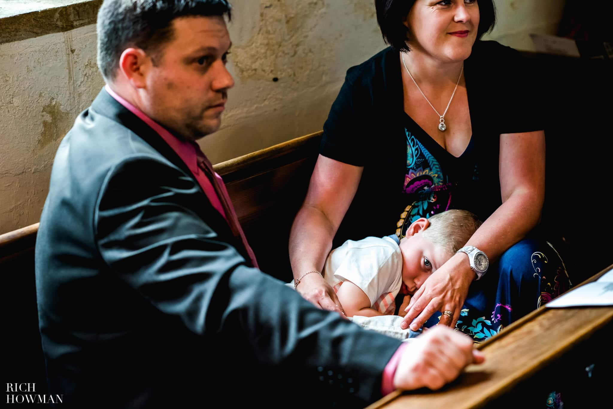 A very tired little boy at a wedding ceremony at All Saints Church Merriott