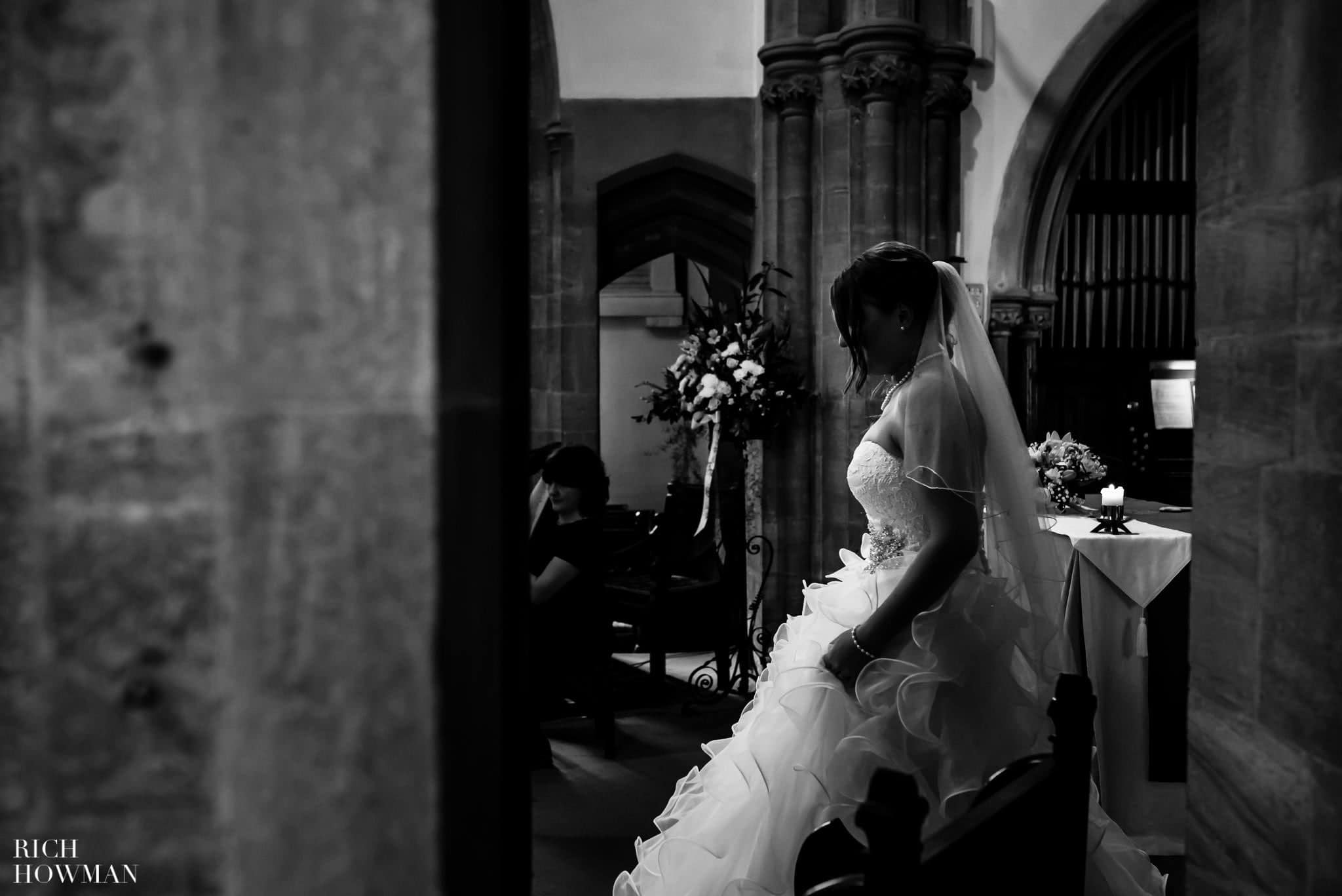 Documentary photograph of the bride walking forward to the vestry of the church to sign the register after getting married