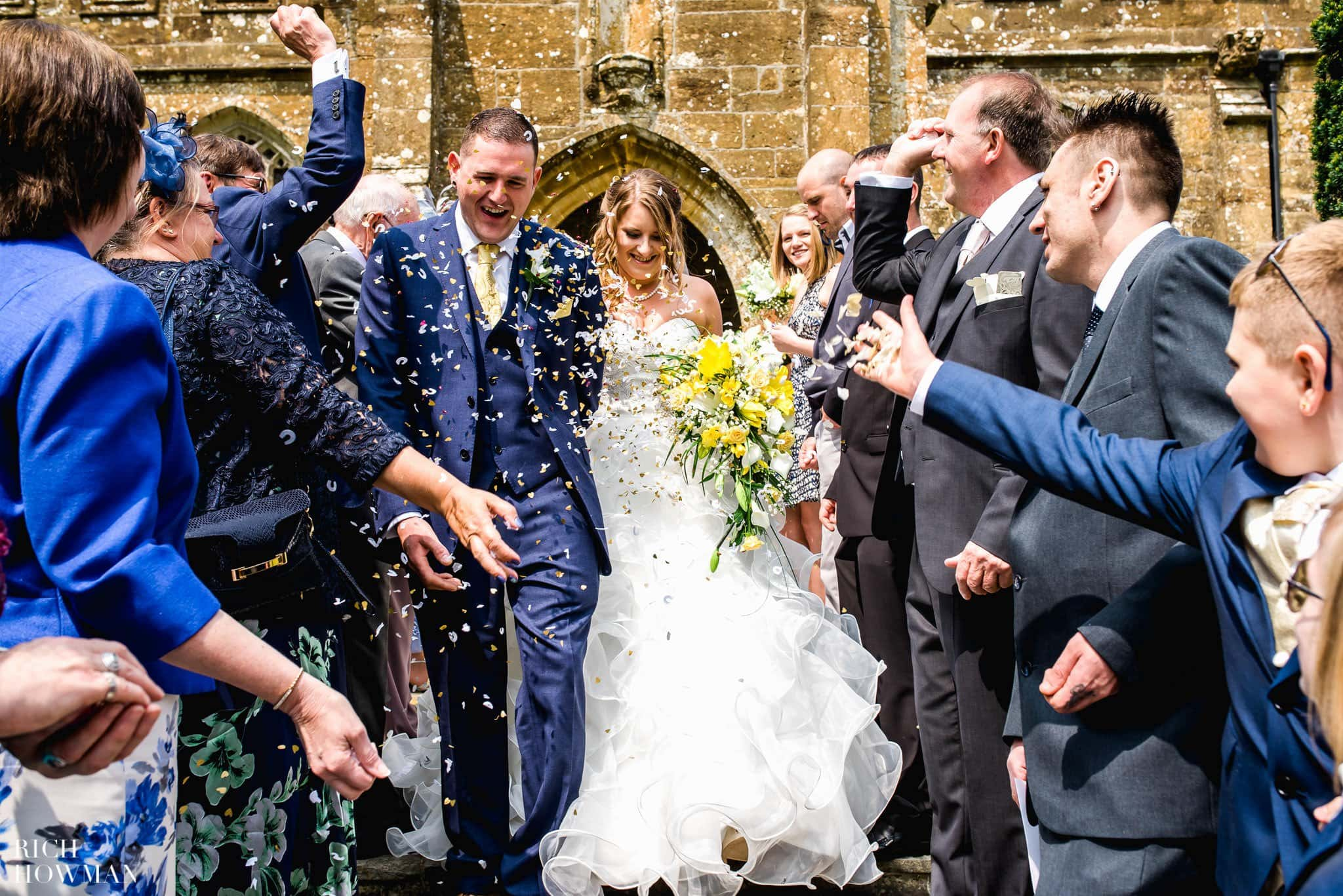 The Bride and Groom running through a shower of confetti after getting married at All Saints Church in Merriott, Somerset