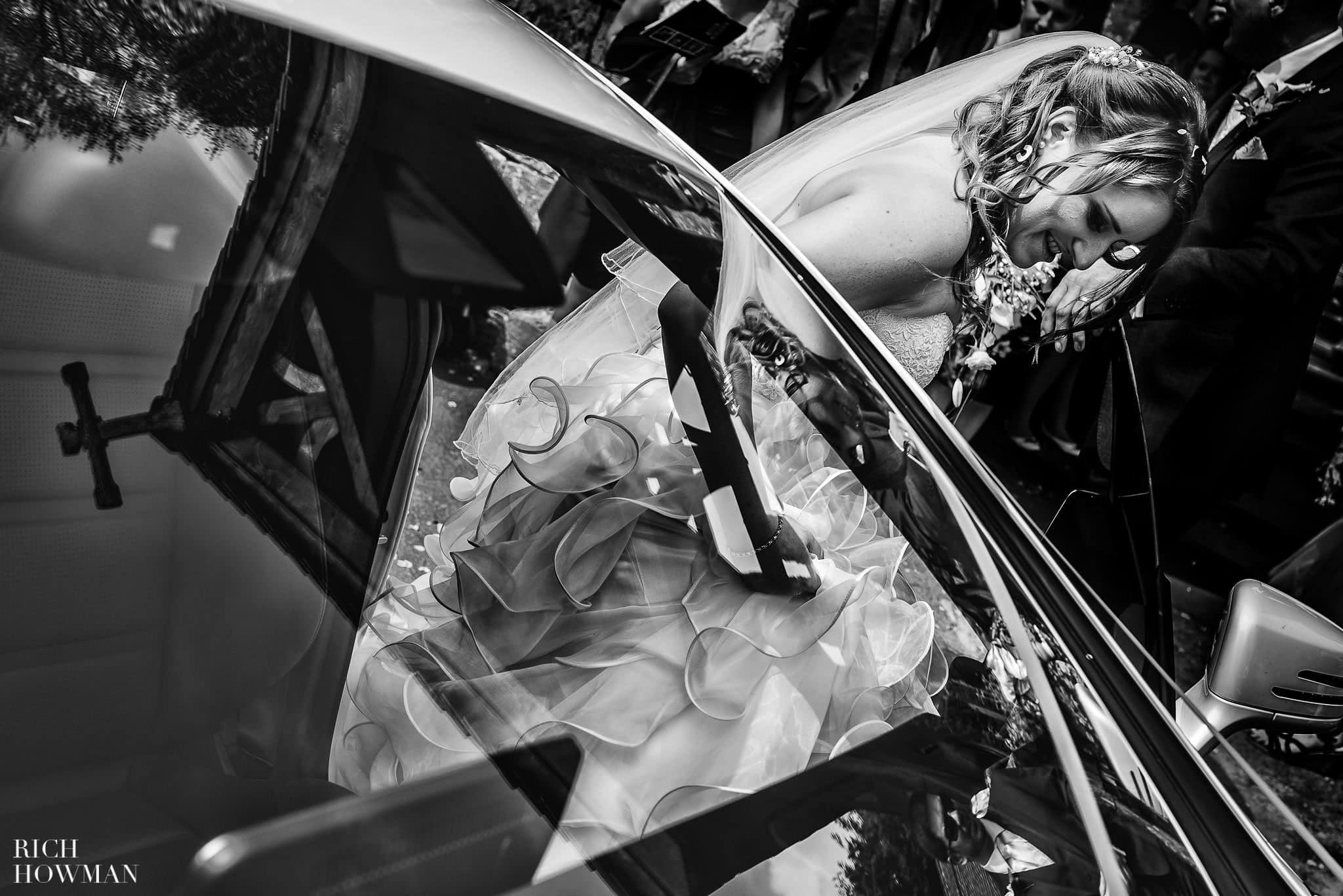 Bride getting in to a white Mercedes after her wedding ceremony on her way to their wedding reception at Haselbury Mill