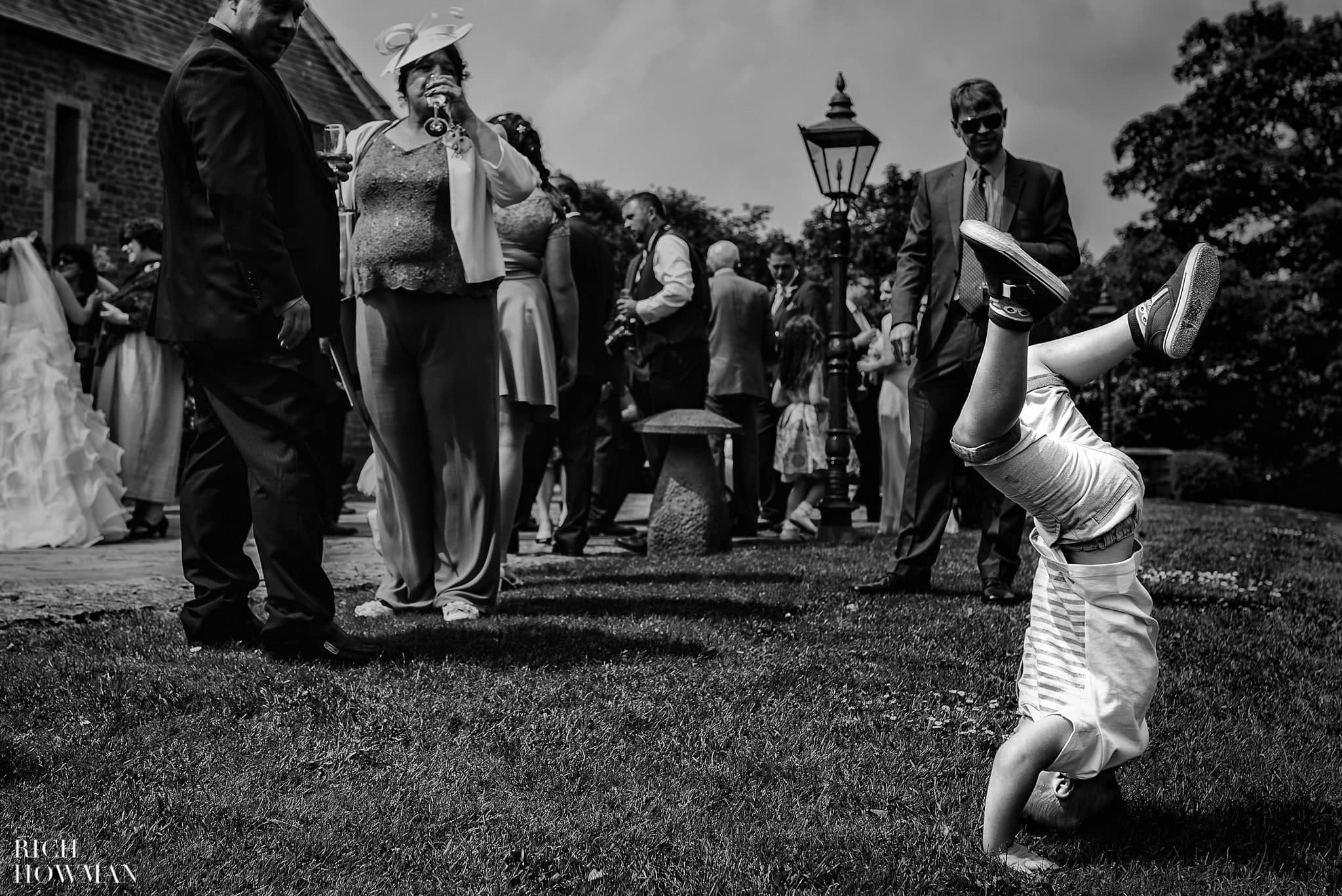 Black and white photo of a little boy standing on his head during a wedding reception at Haselbury Mill
