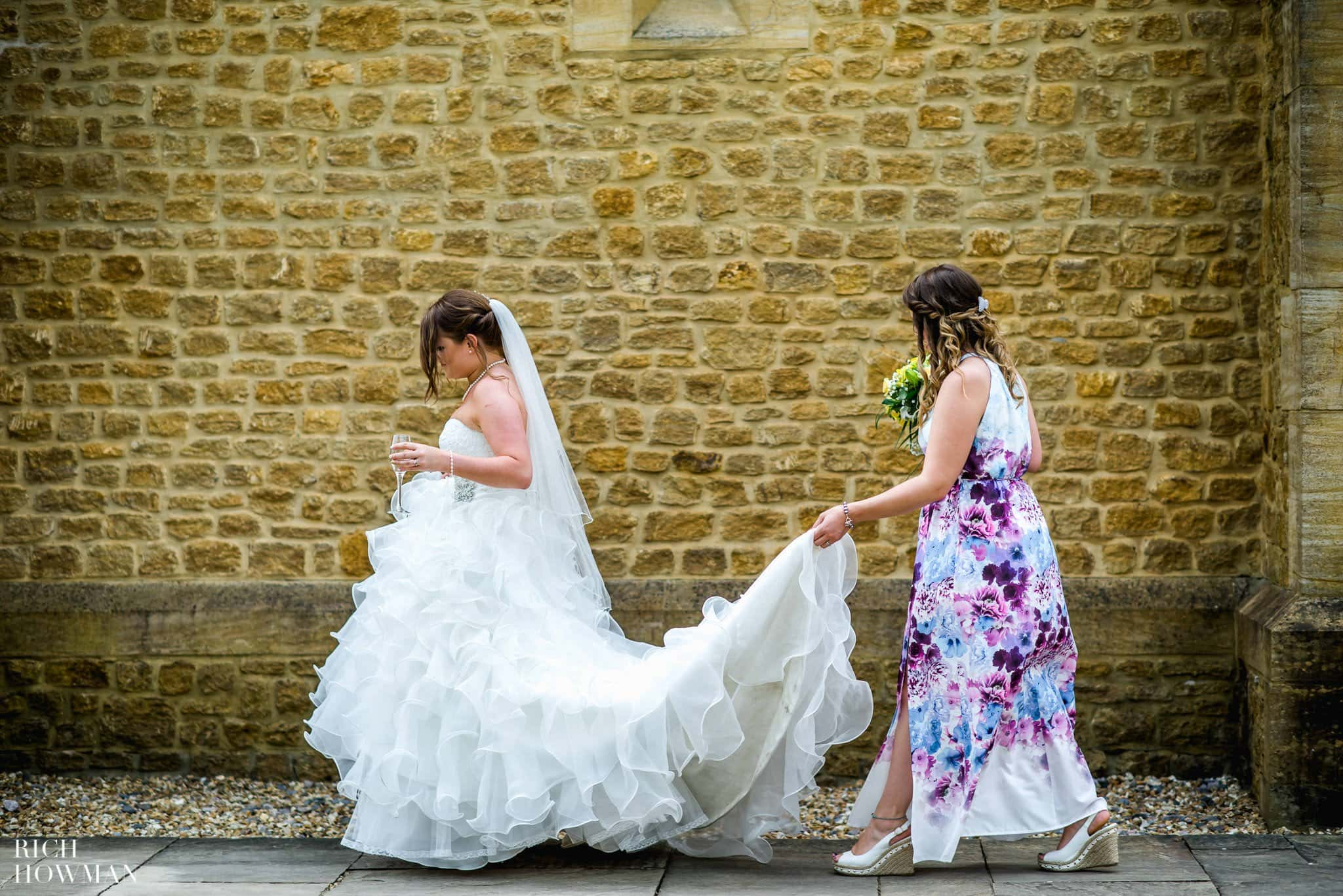 Bridesmaid holding the brides dress for her as she walks