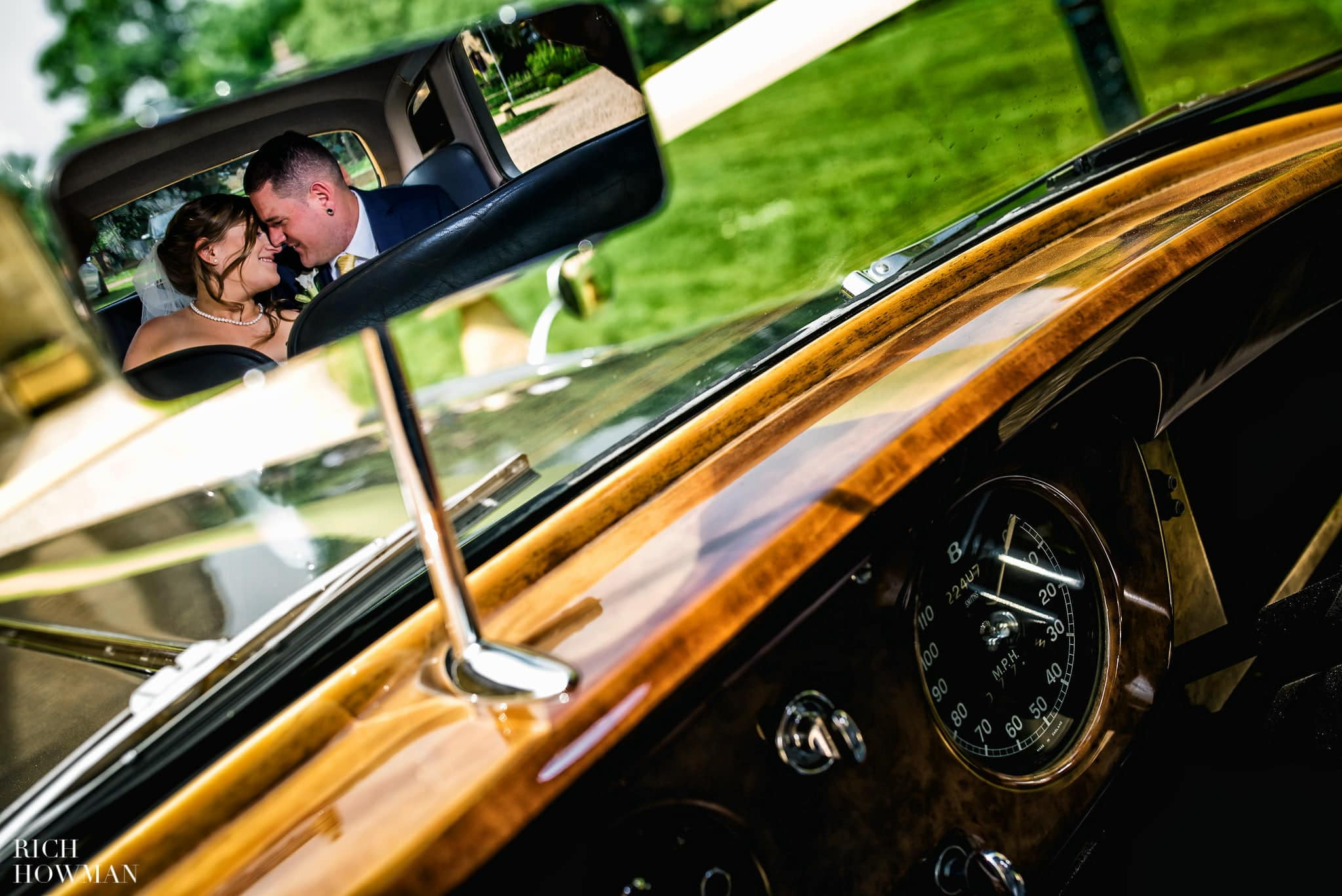 Newly married bride and groom creative portrait, reflected in the rear view mirror of a vintage Bentley