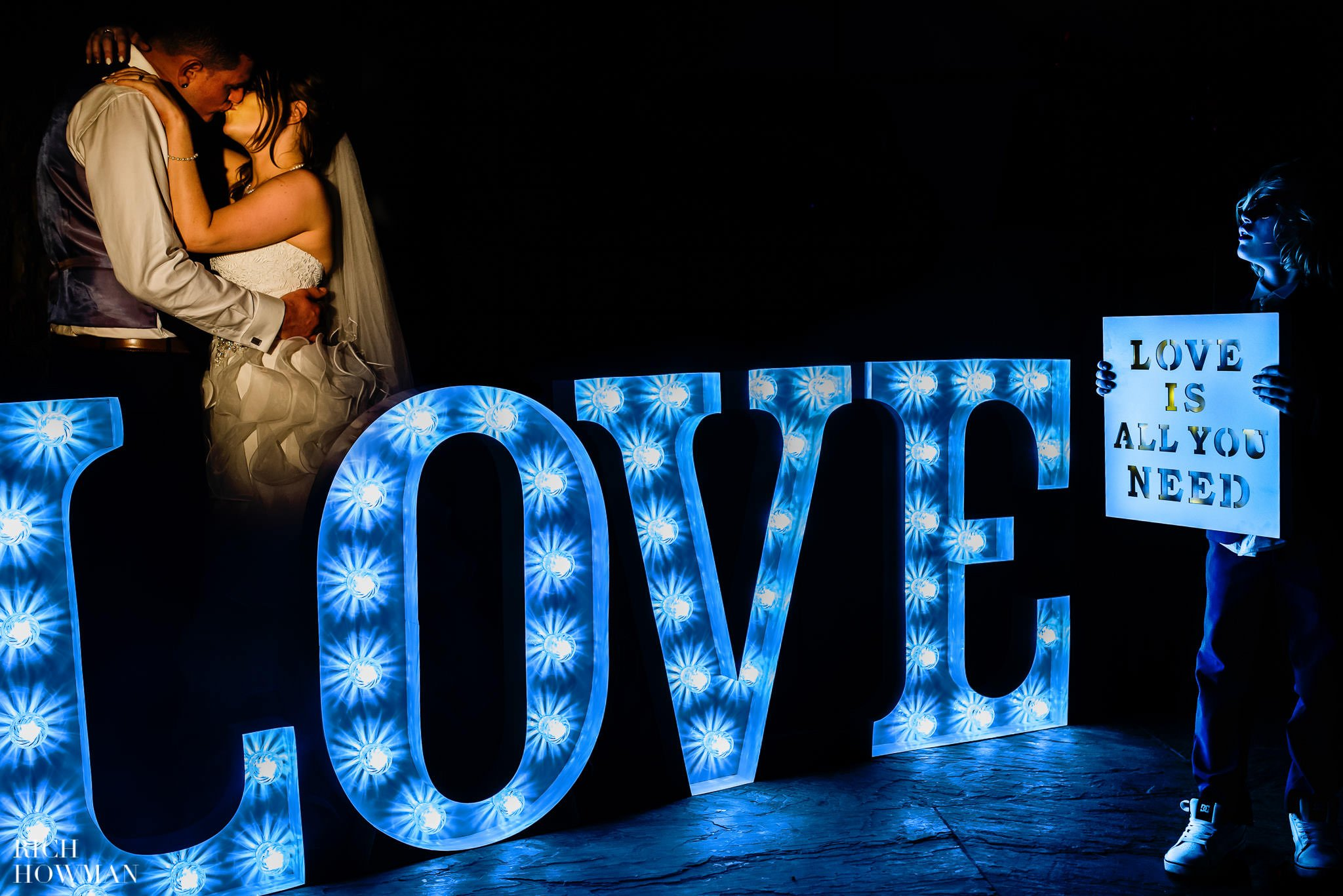 Little boy holding an 'all you need is love' sign during a wedding at Haselbury Mill as the happy couple kiss behind a giant love sign