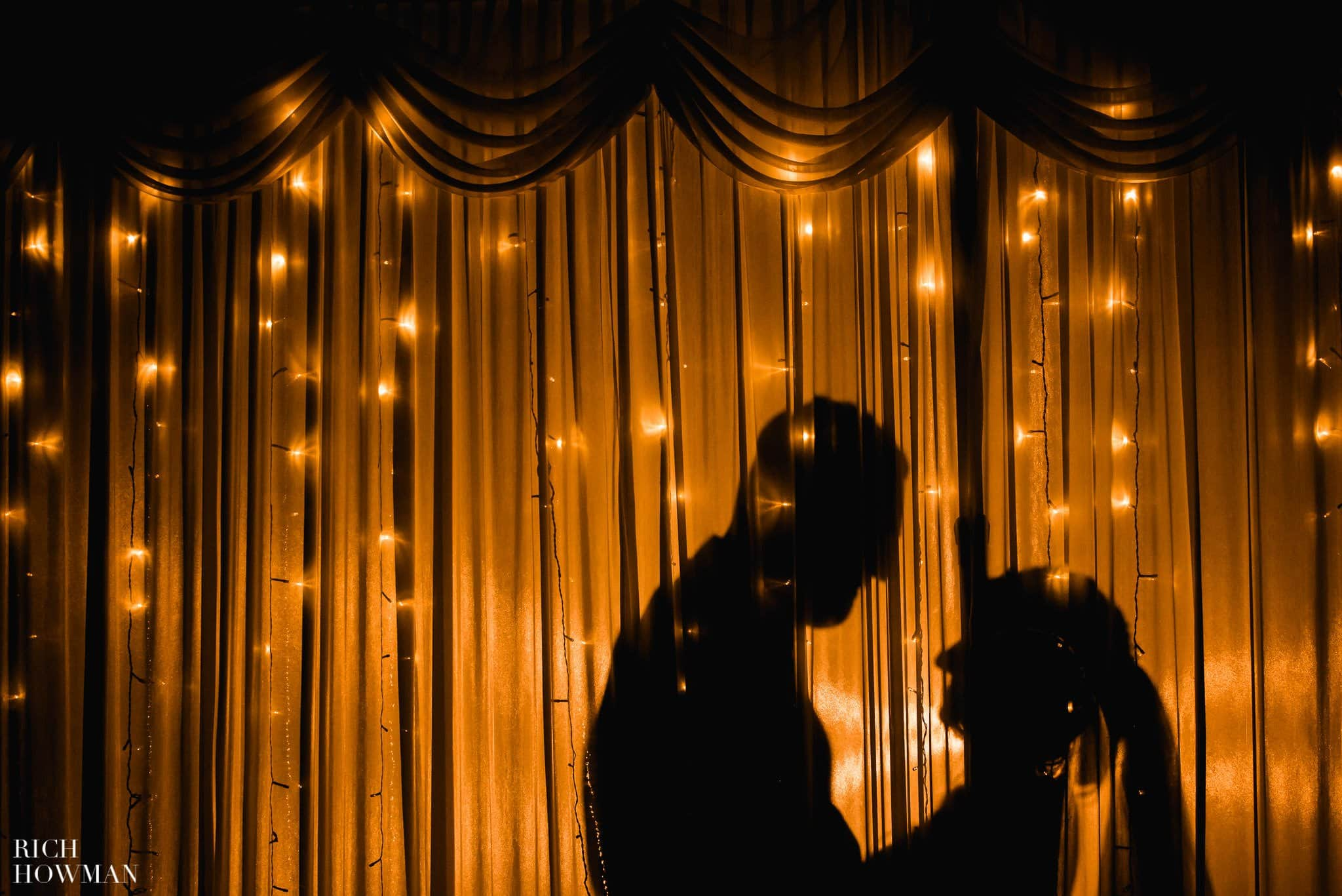 Newlyweds silhouetted on curtains during their wedding reception