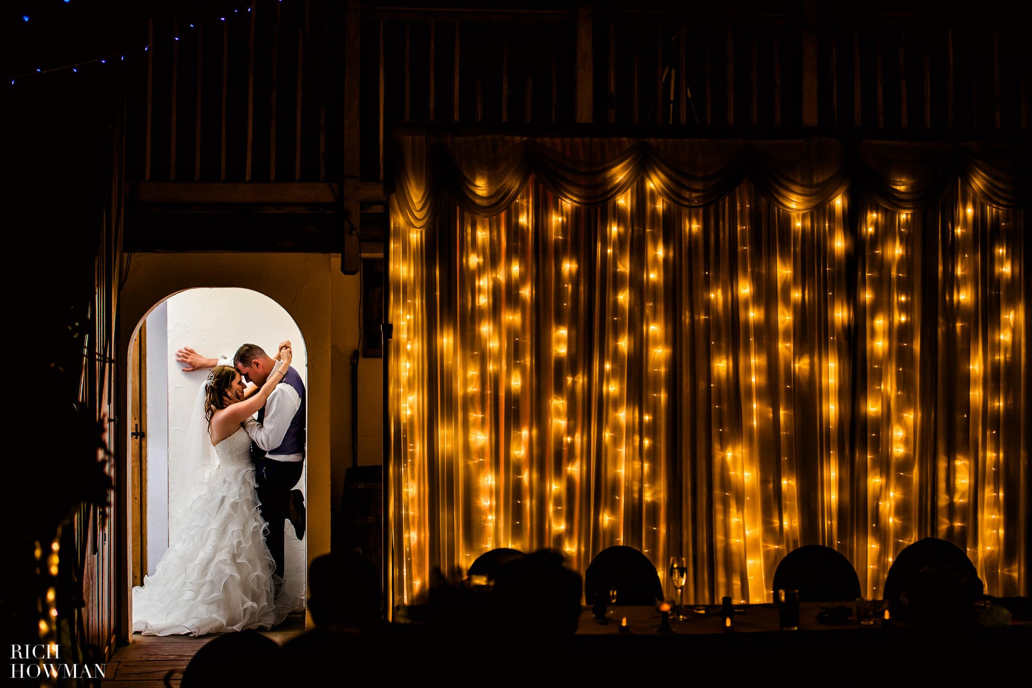 Couple snuggling in a doorway during their wedding