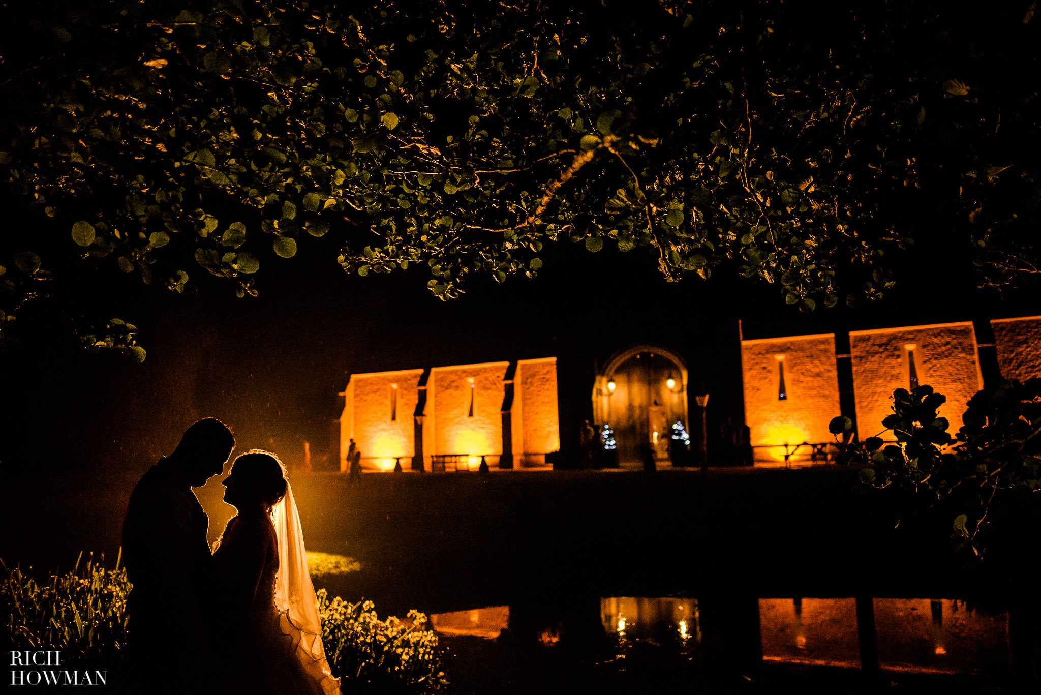 Bride and groom photographed at night, silhouetted in front of Haselbury Mill