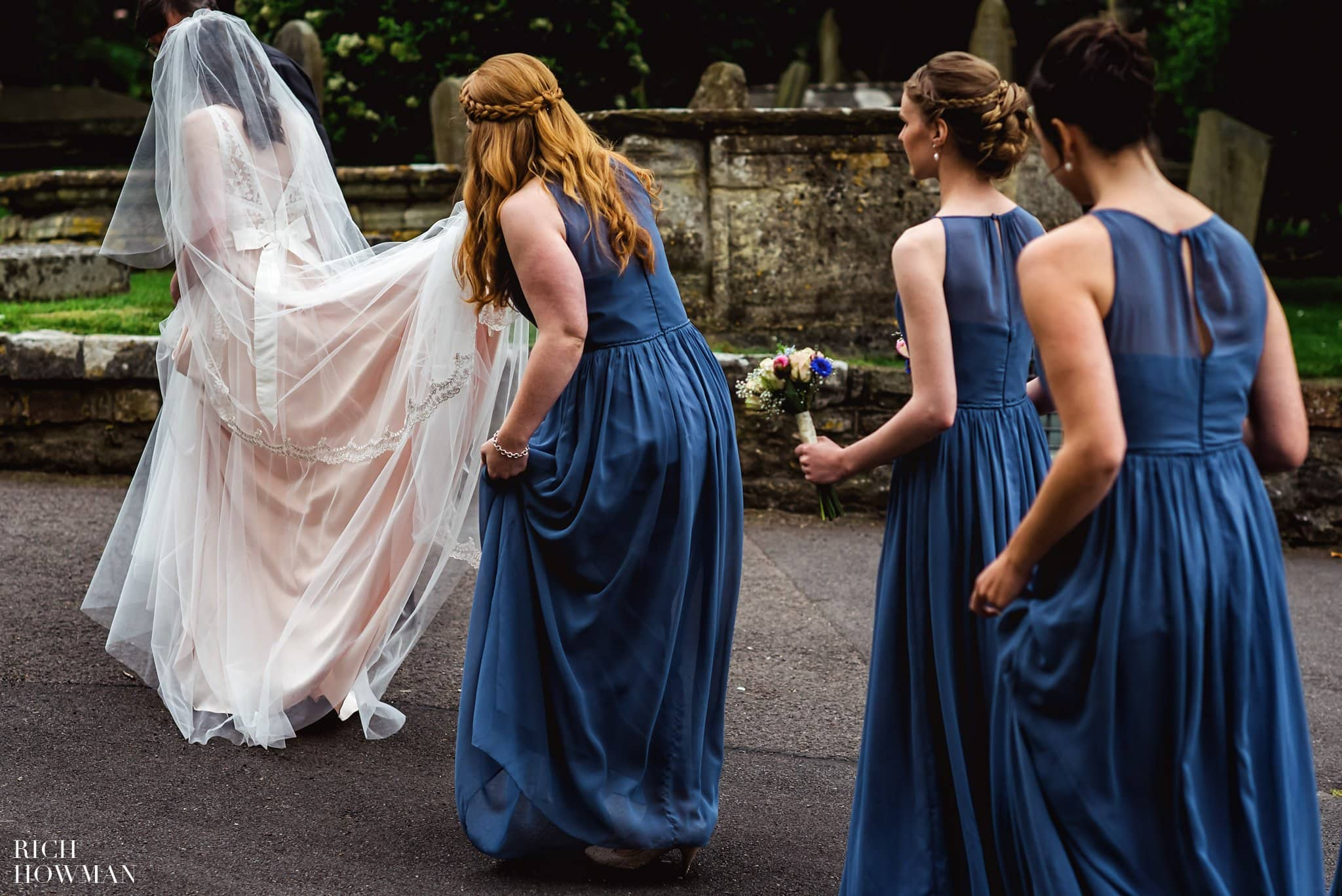 Bridesmaids in blue helping the bride with her dress before her wedding at