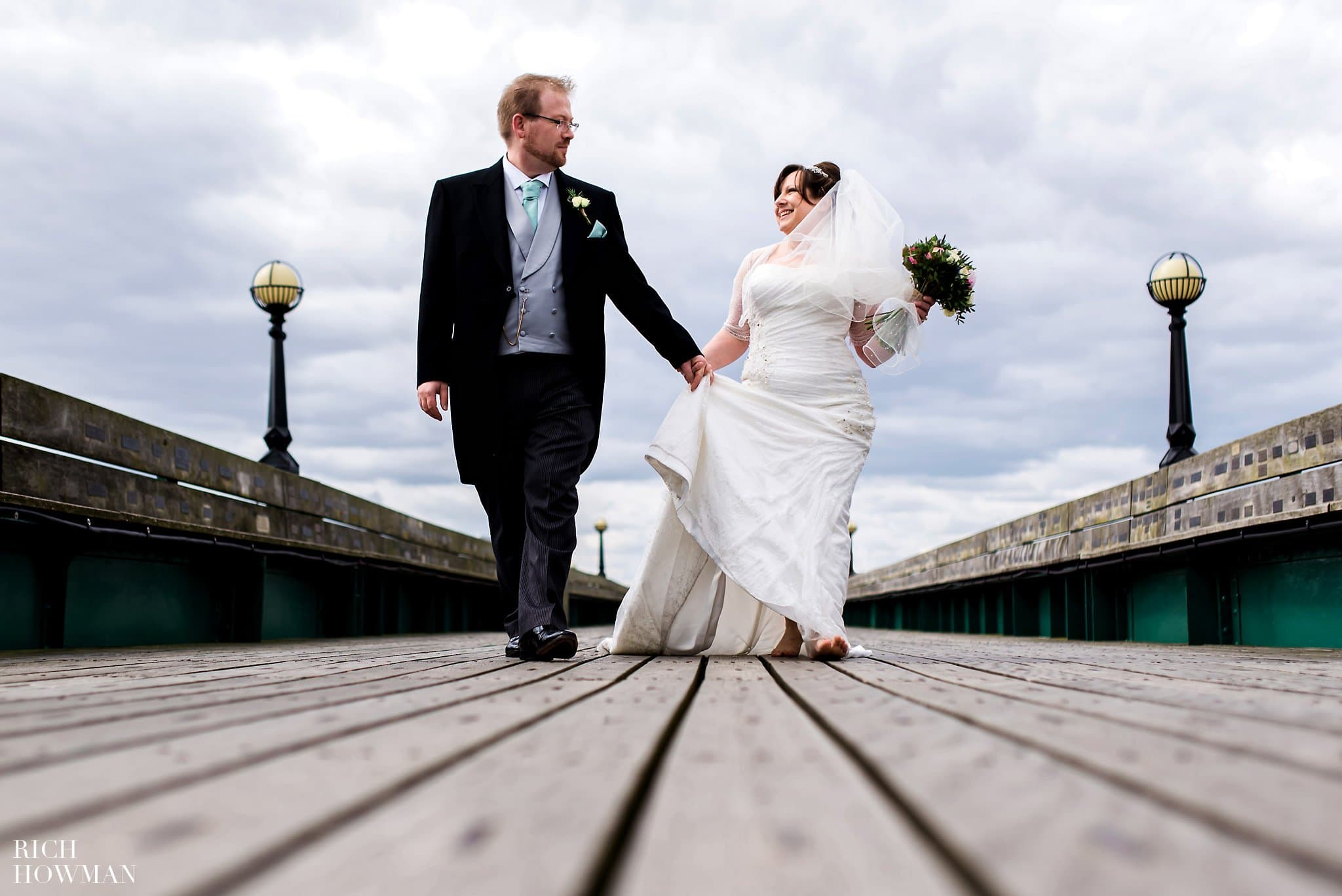 Clevedon Pier Wedding Photos Bride and Groom walking on pier