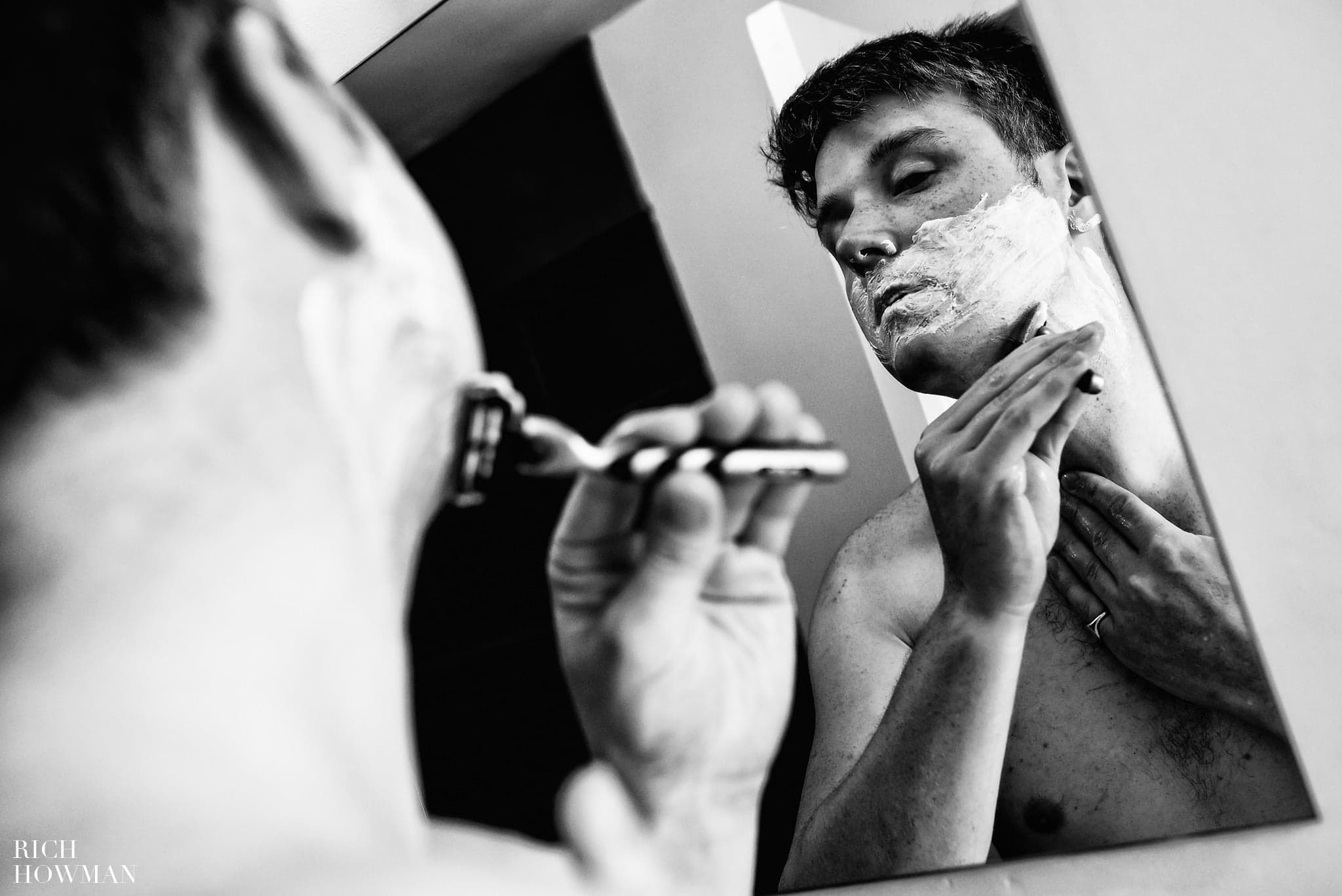 Groom shaving reflected in a mirror before wedding