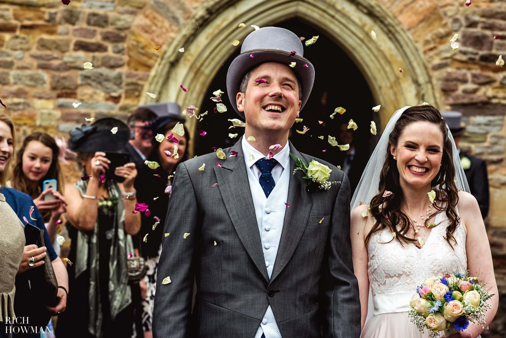 Guests throwing confetti over the bride and groom outside the church in Bristol