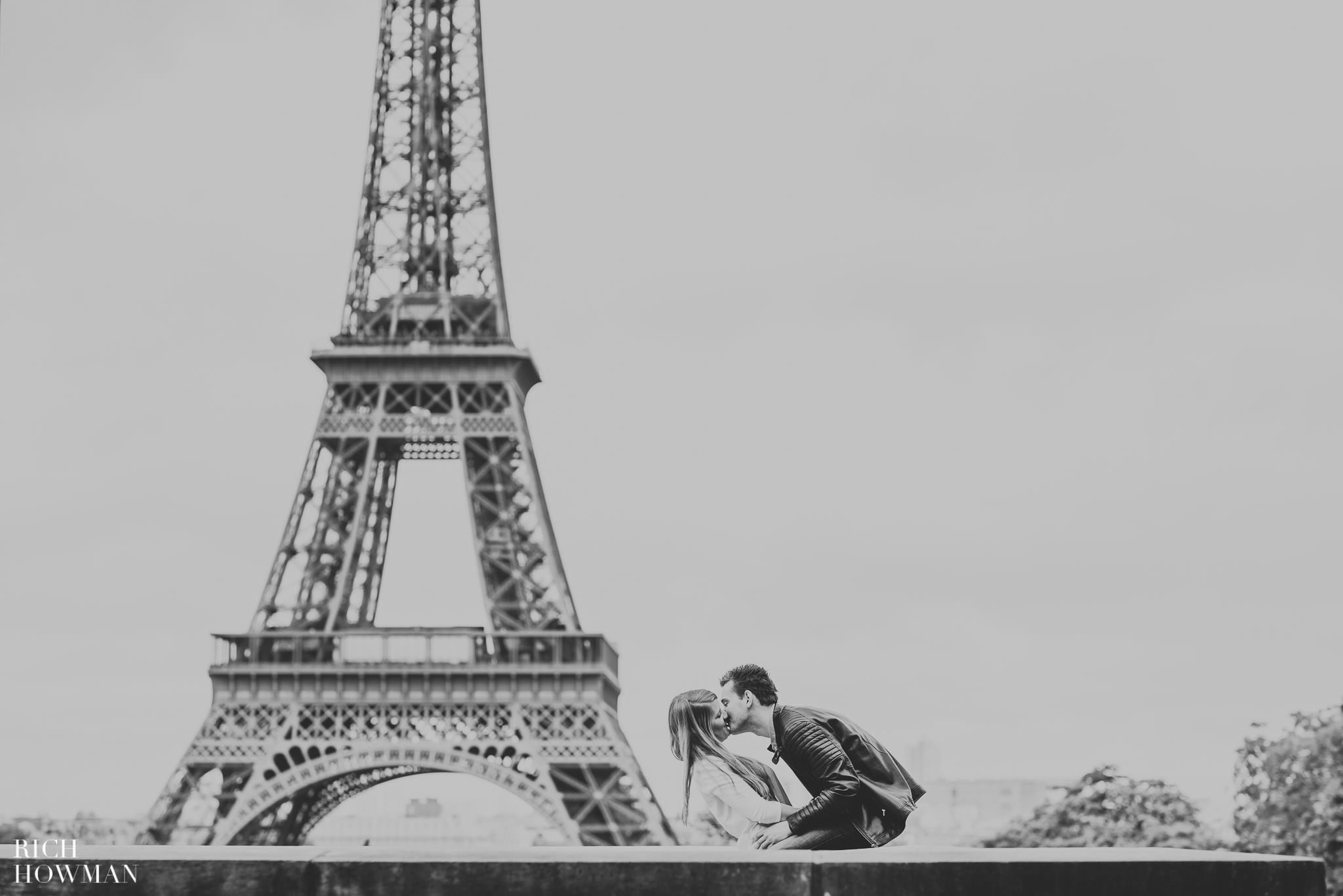 Black and white photograph of a couple kissing at the Eiffel Tower, Paris