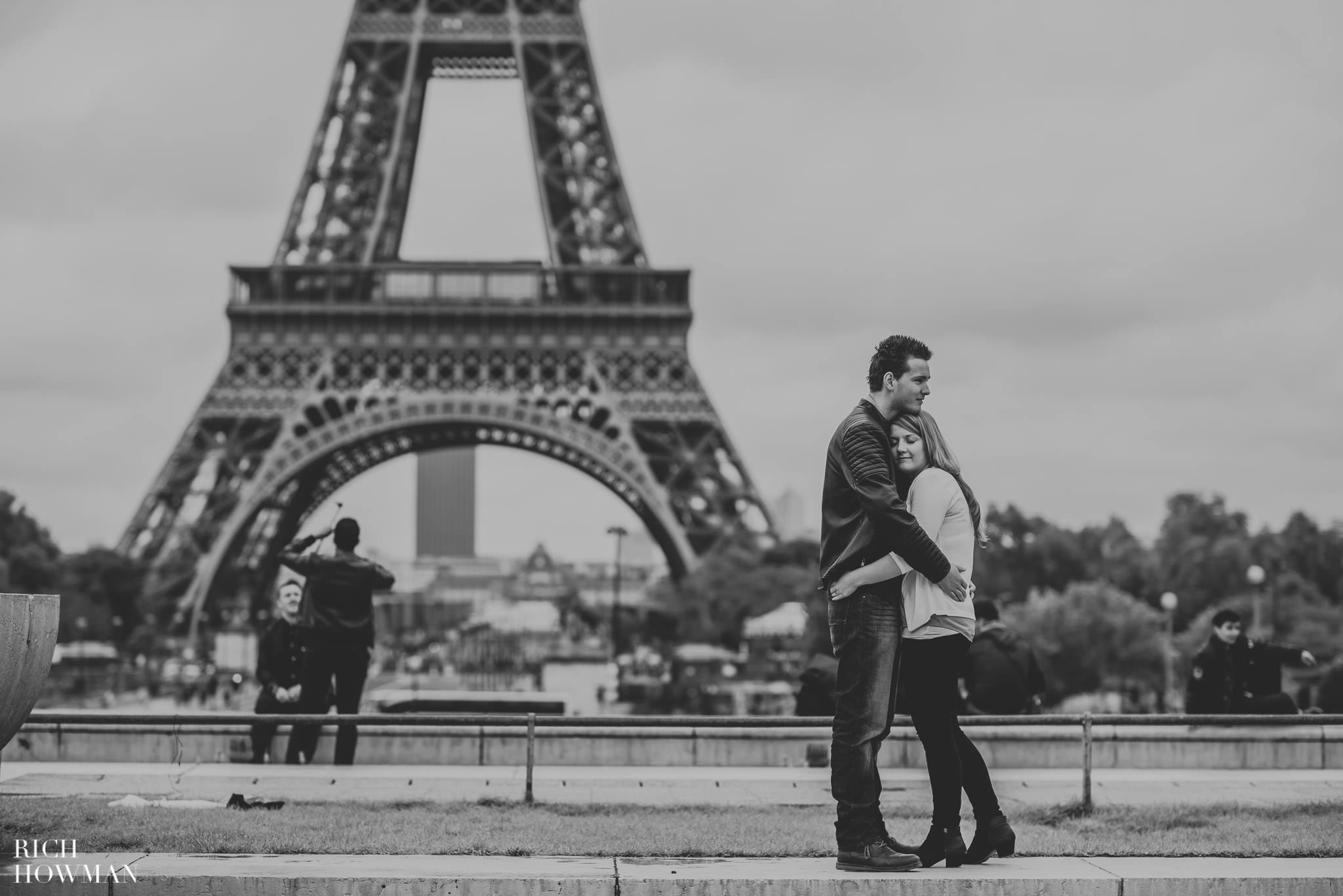 Black and white photo of a couple hugging at the eiffel tower