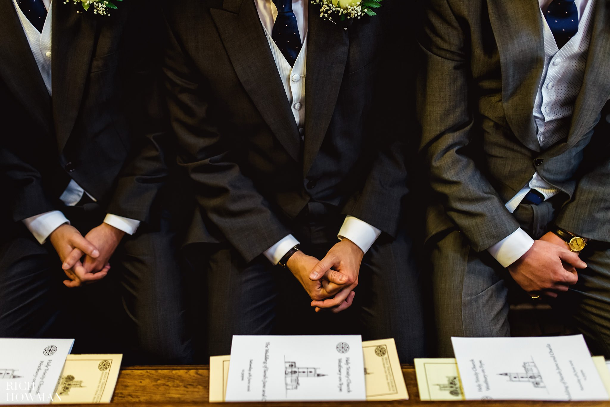 groomsmens hands clasped whilst waiting in the church