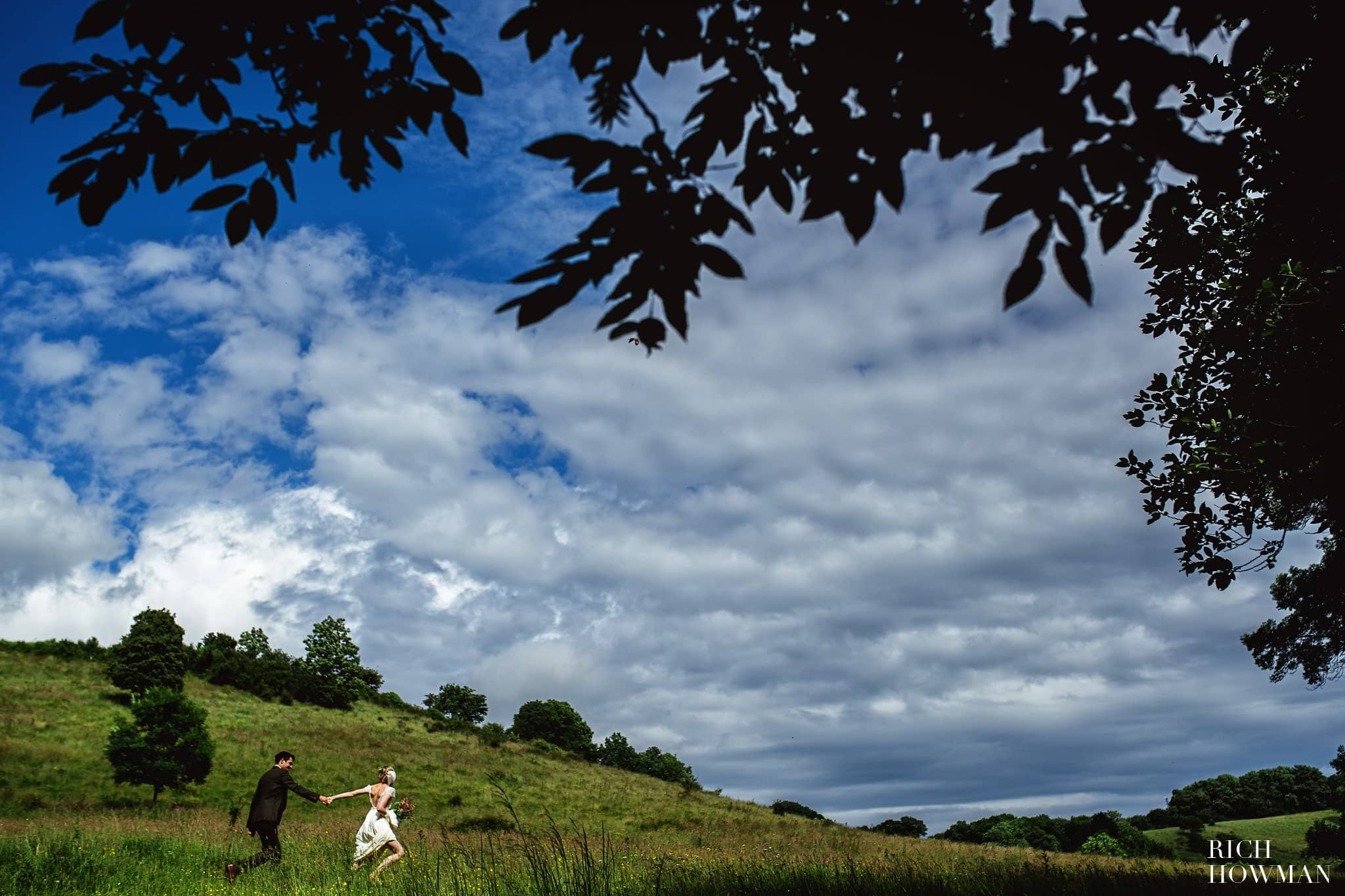 Wedding Photographer Folly Farm Bristol - Bride pulling her husband through the fields under a blue sky