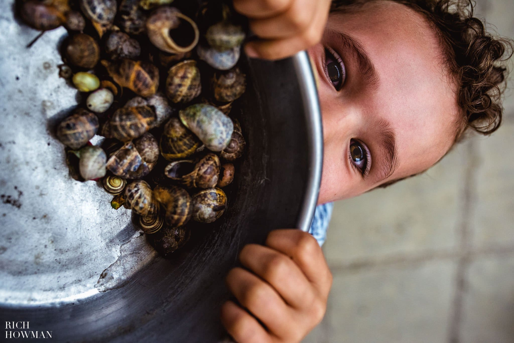 Little boy at a wedding with a bowl full of snails