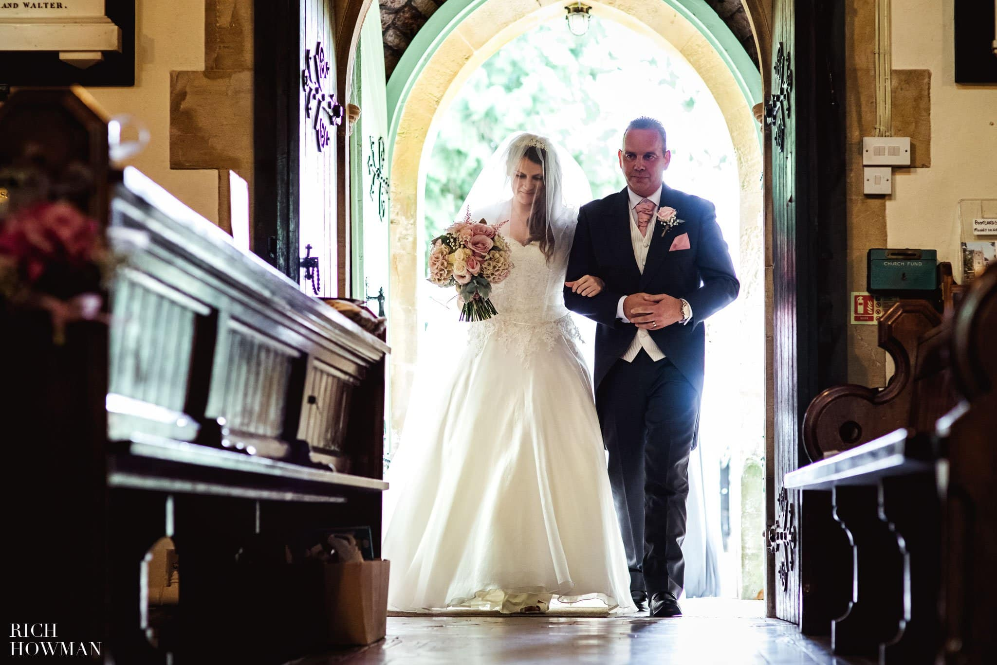 Wedding photograph of the bride and her dad in the Church doorway for her wedding at St. James' Church in Ashwick