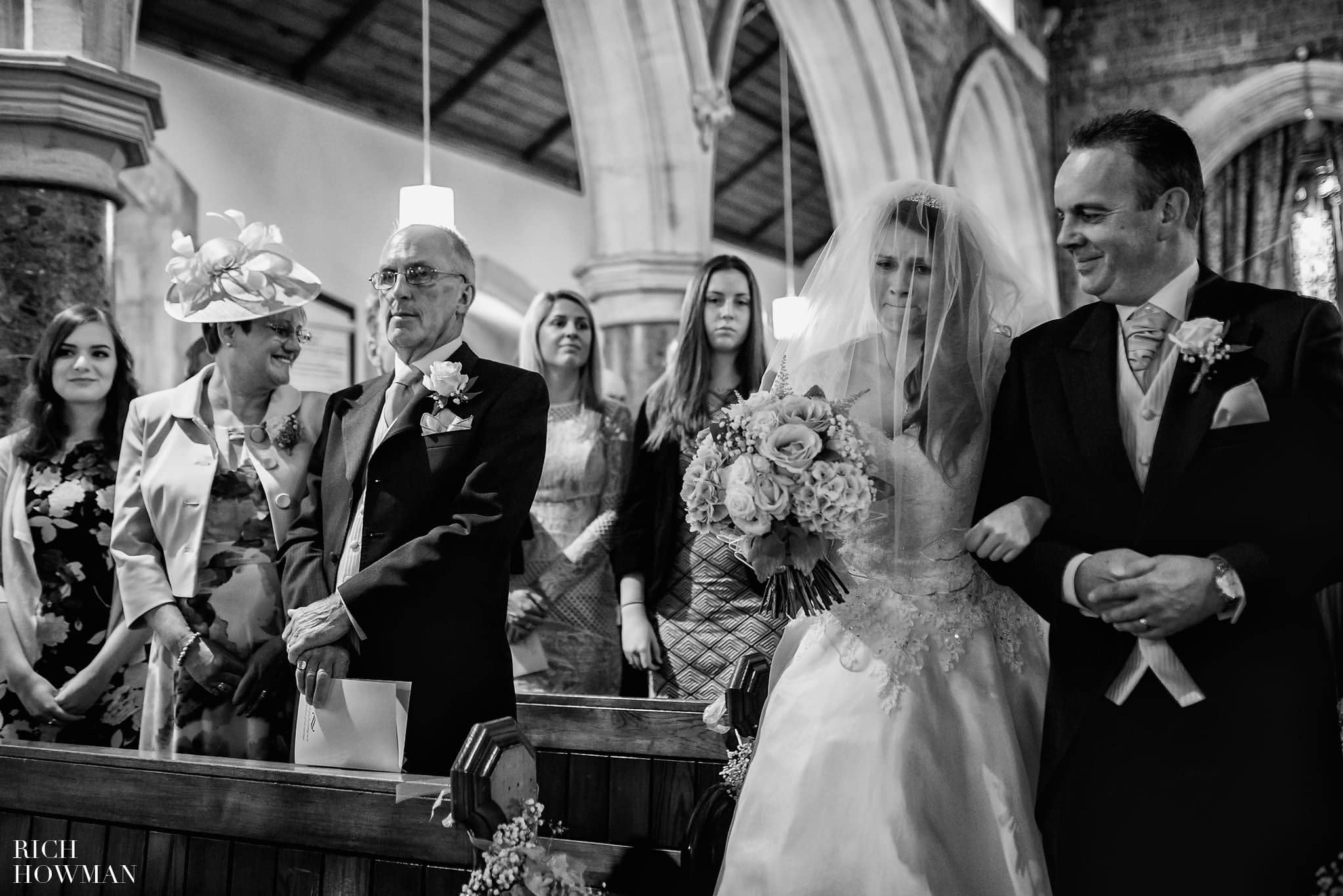 Documentary wedding photo of the bride walking up the aisle in church to meet her waiting fiancée