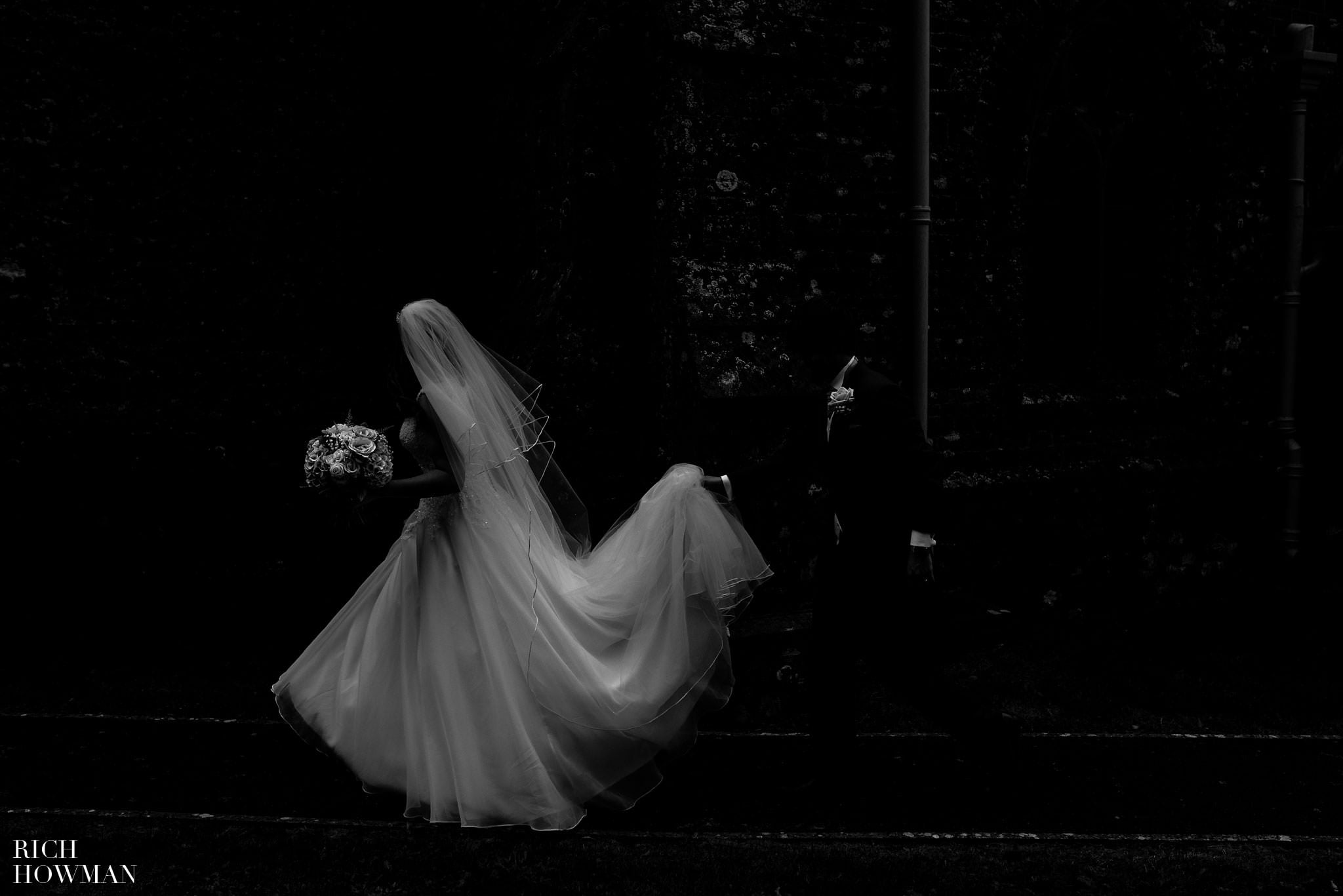 Creative black and white wedding photograph of the bride walking past the church with the groom helping her hold her wedding dress