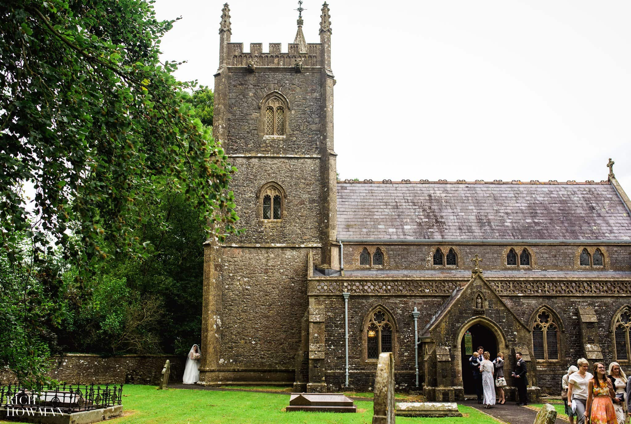 The married couple hide around the corner of the St. James' Church Ashwick to allow their wedding guests to leave and form a confetti line