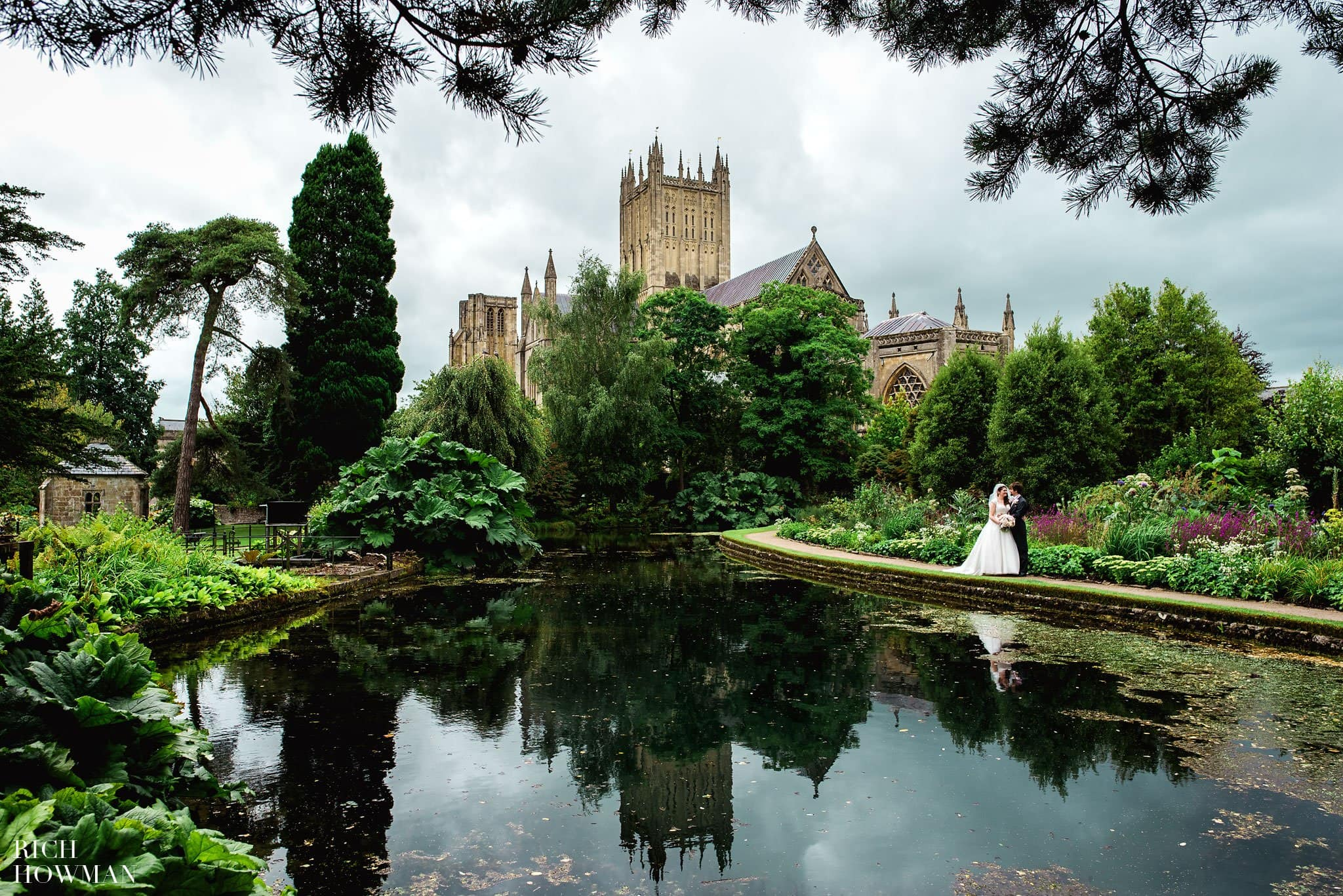 Wedding Photographer at the Bishops Palace photographing the bride and groom with Wells cathedral in the background