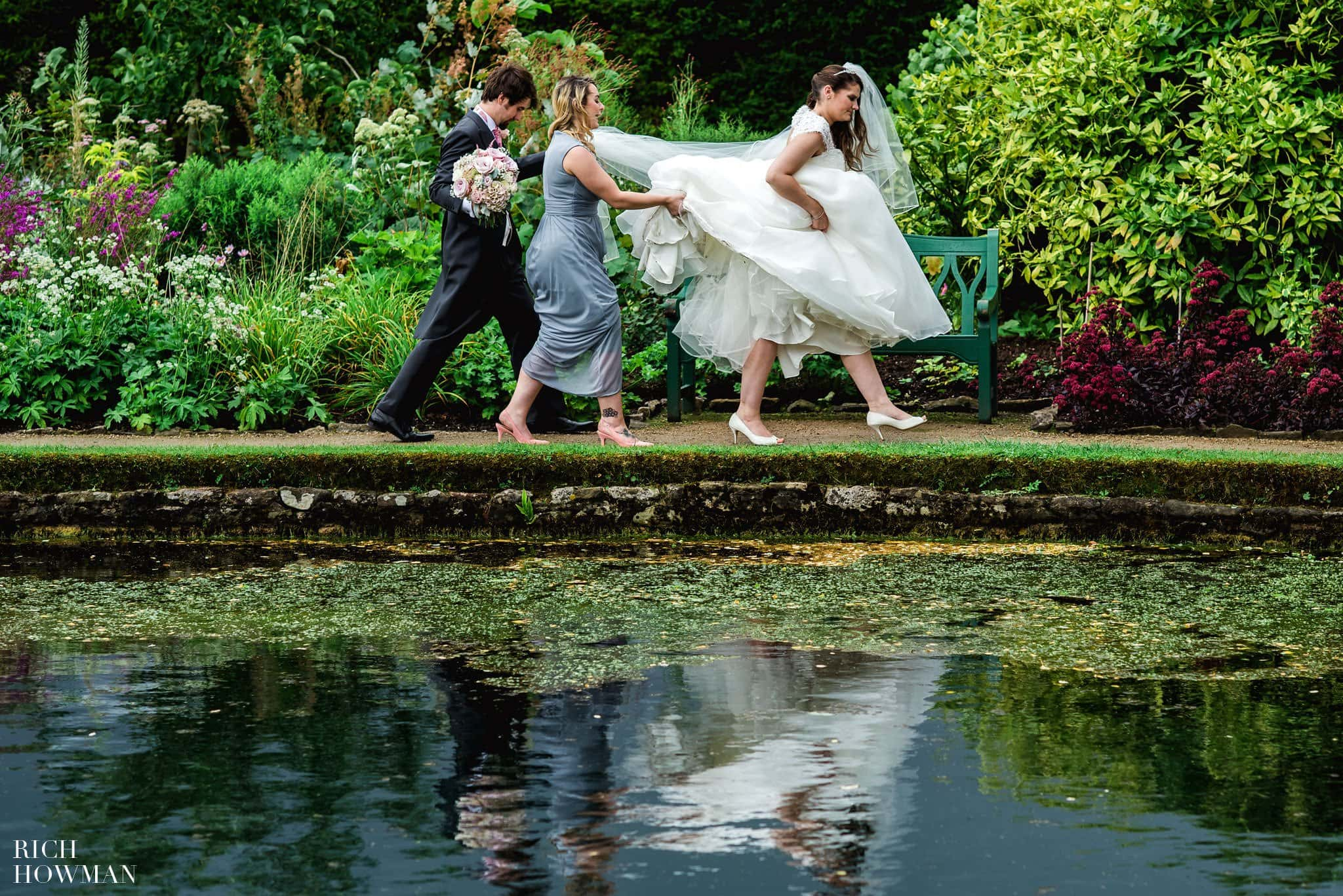 Bride and groom reflected in the lake in the grounds of the Bishops Palace
