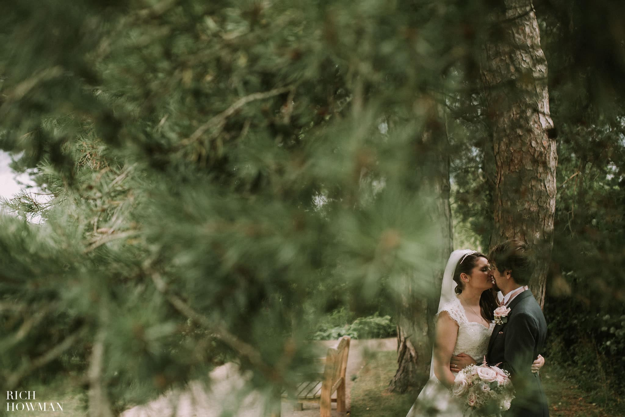Couple kissing during their wedding photos in the grounds of the Bishops Palace