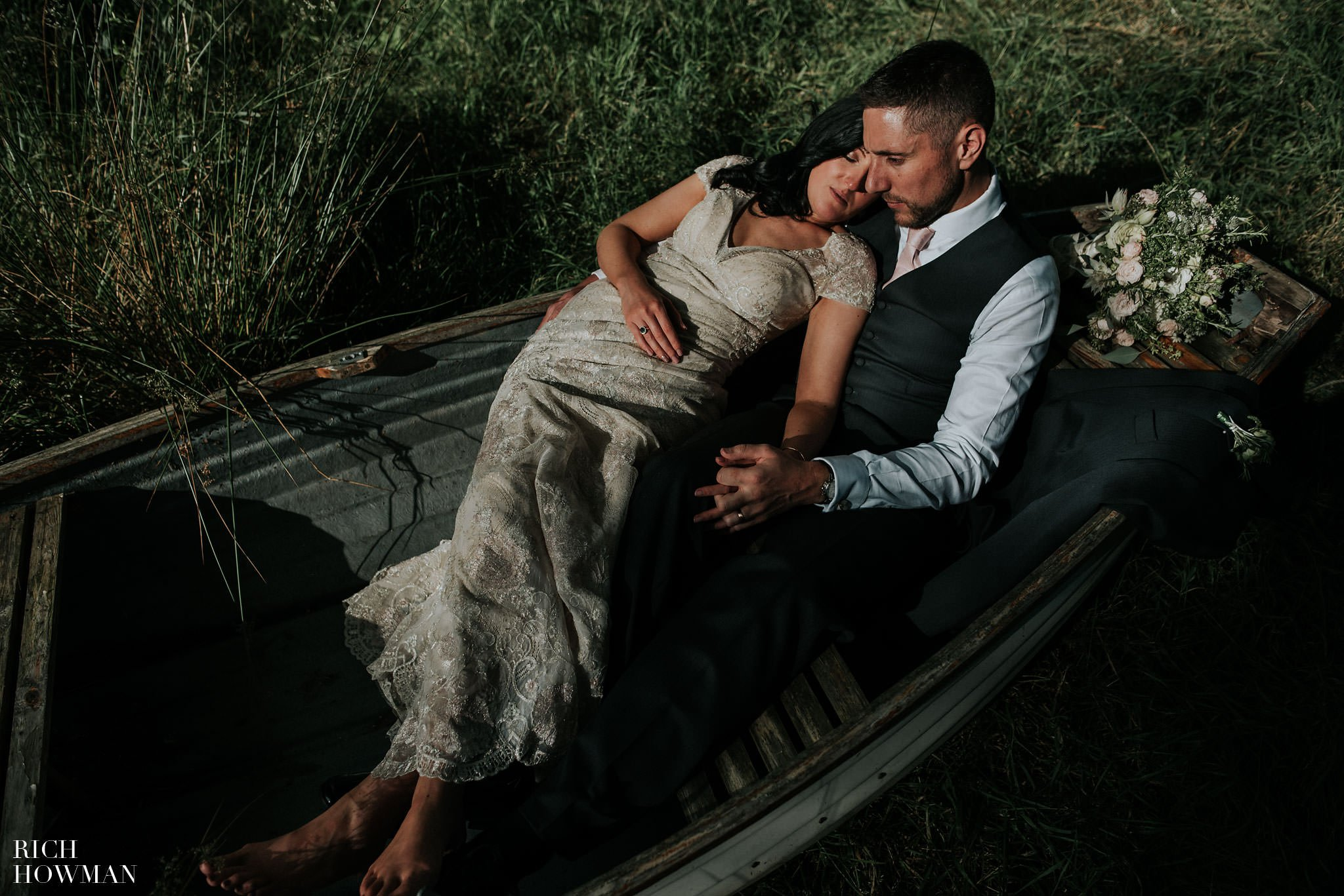 Bride and groom laying in a rowing boat at Iscoyd Park