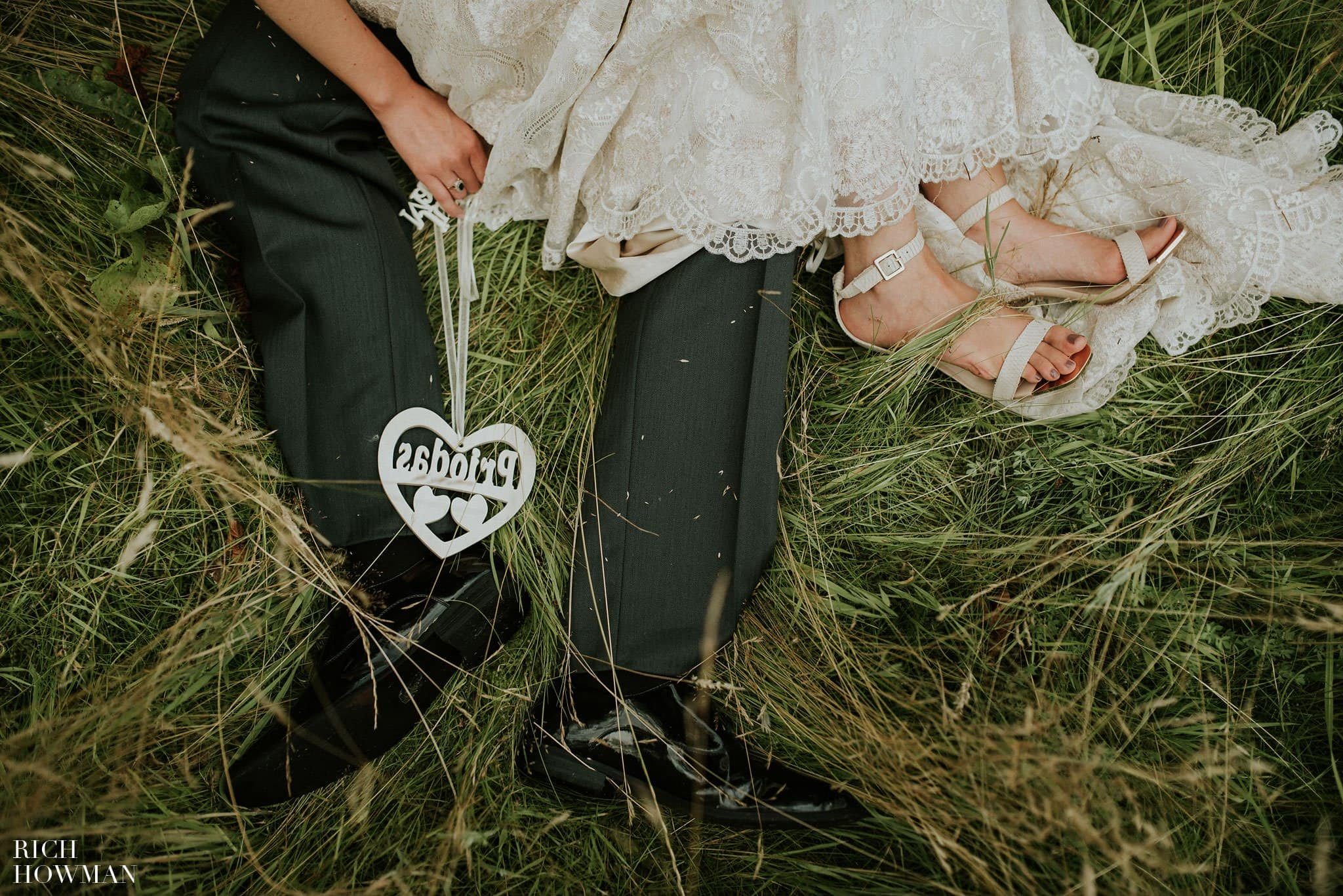 Photograph of the couples feet sitting in the grass during their Iscoyd Park Wedding - Photo by Rich Howman