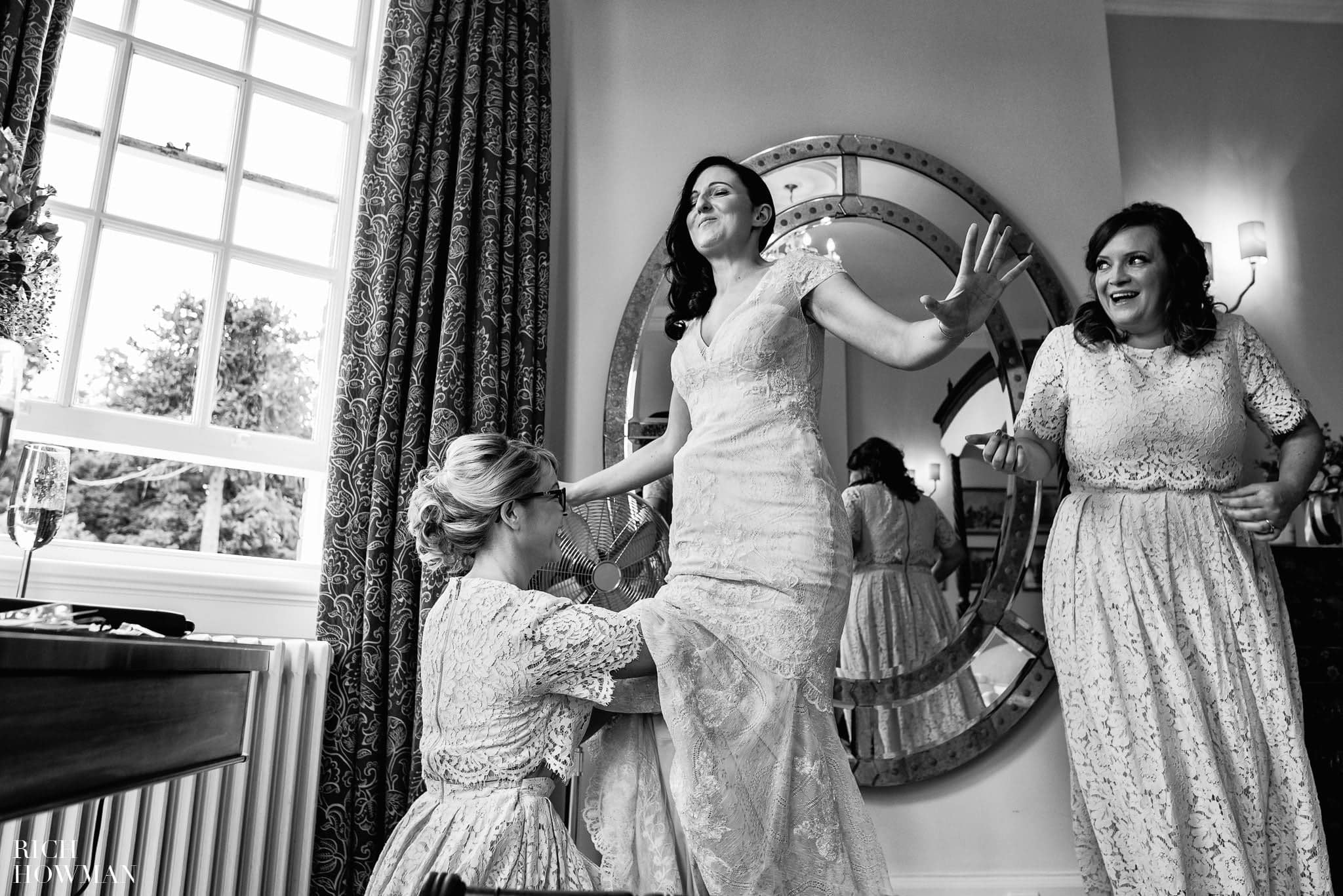 Funny black and white photo of the bride getting her dress on