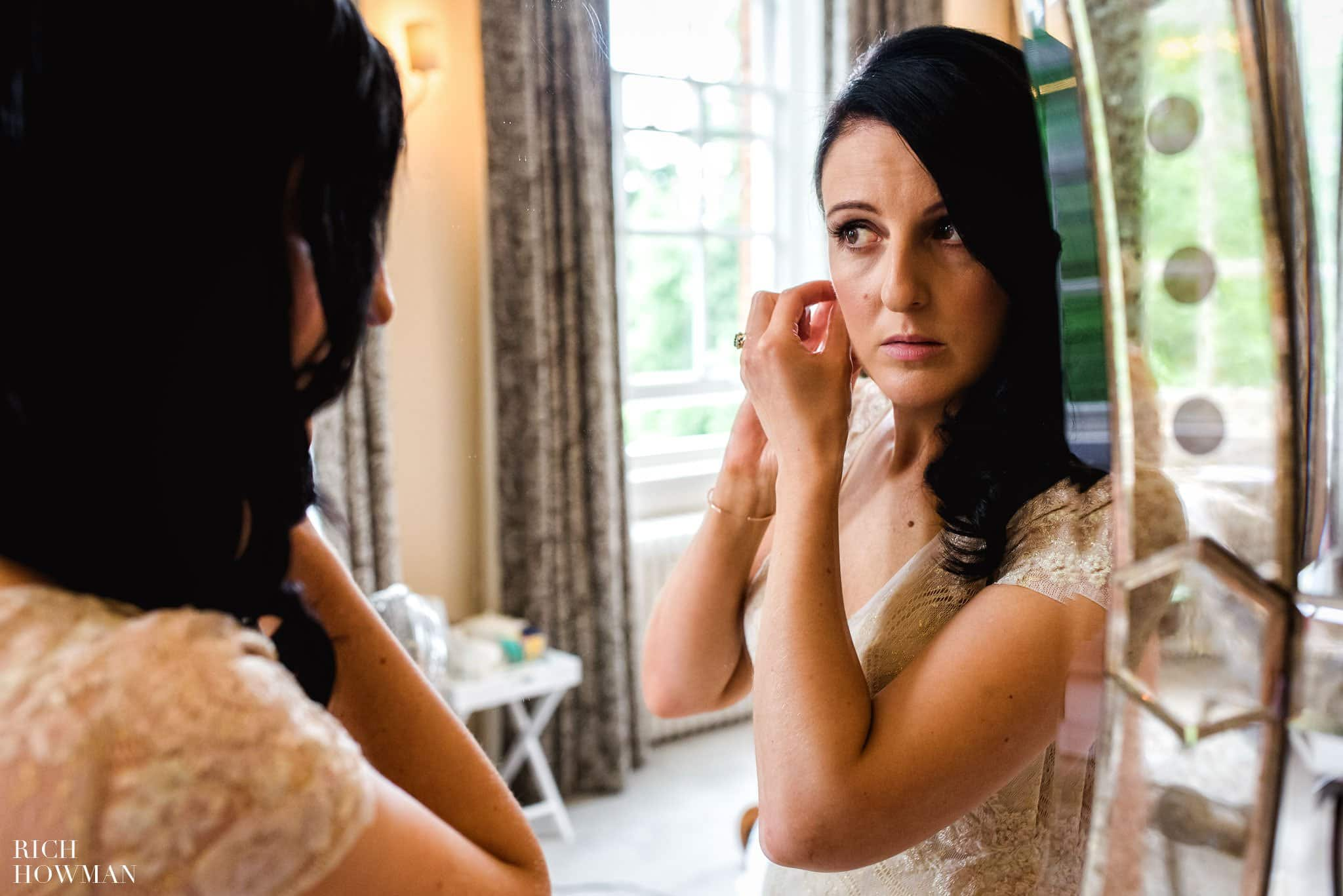 Bride putting on her earrings reflected in a mirror