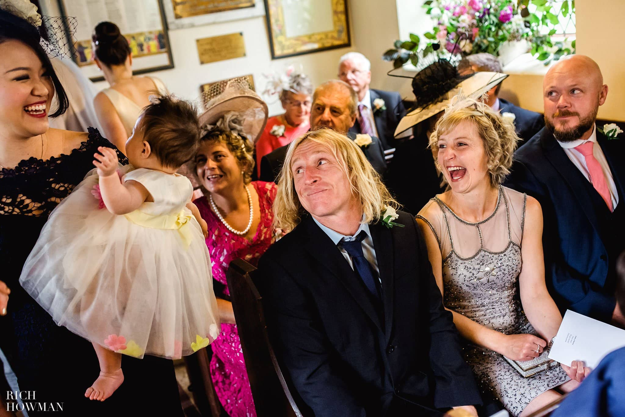 Wedding guests laughing at a baby in St Mary's Church, Whitewell