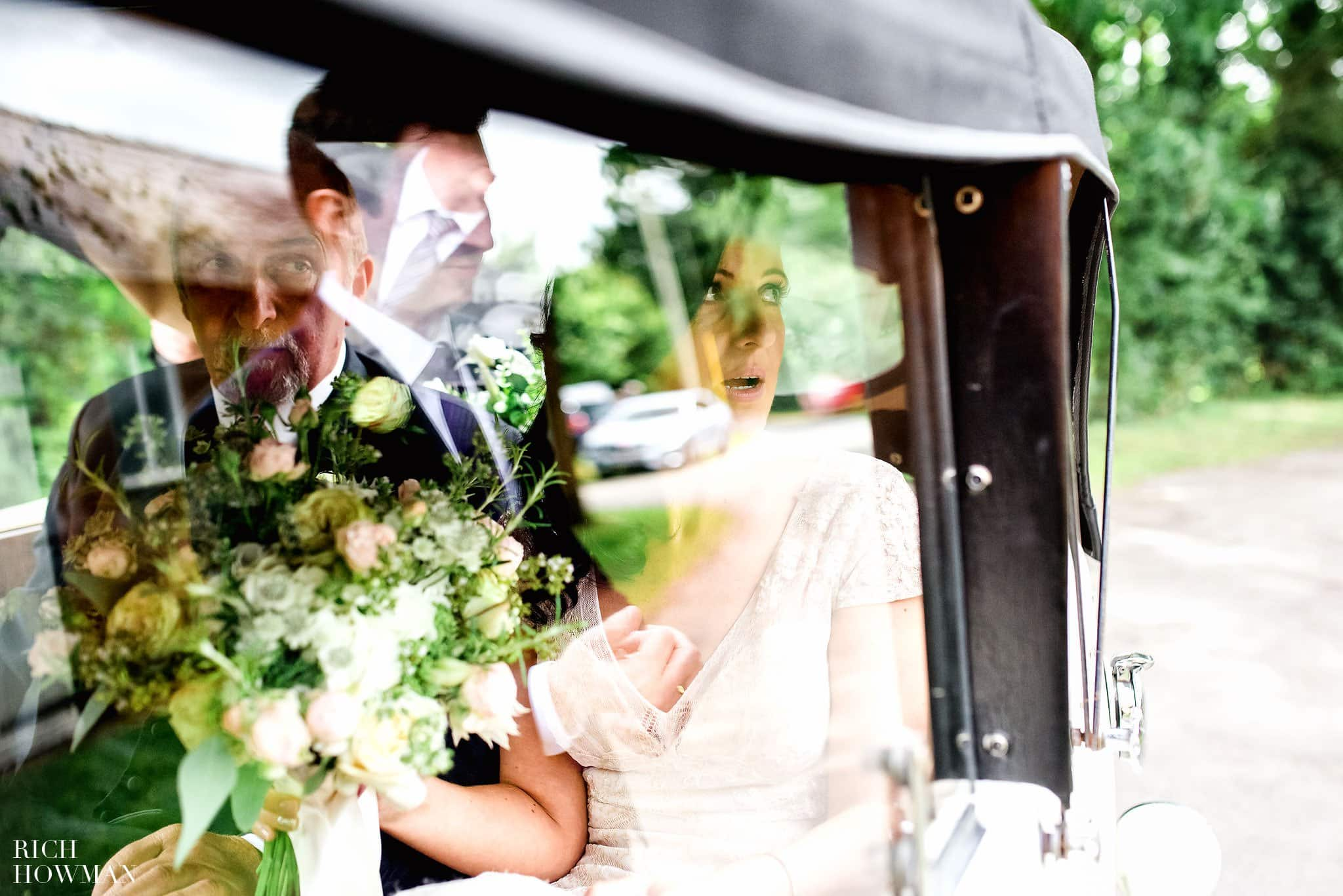 Bride and her father reflected through the car window before her wedding at St Mary's Church, Whitewell