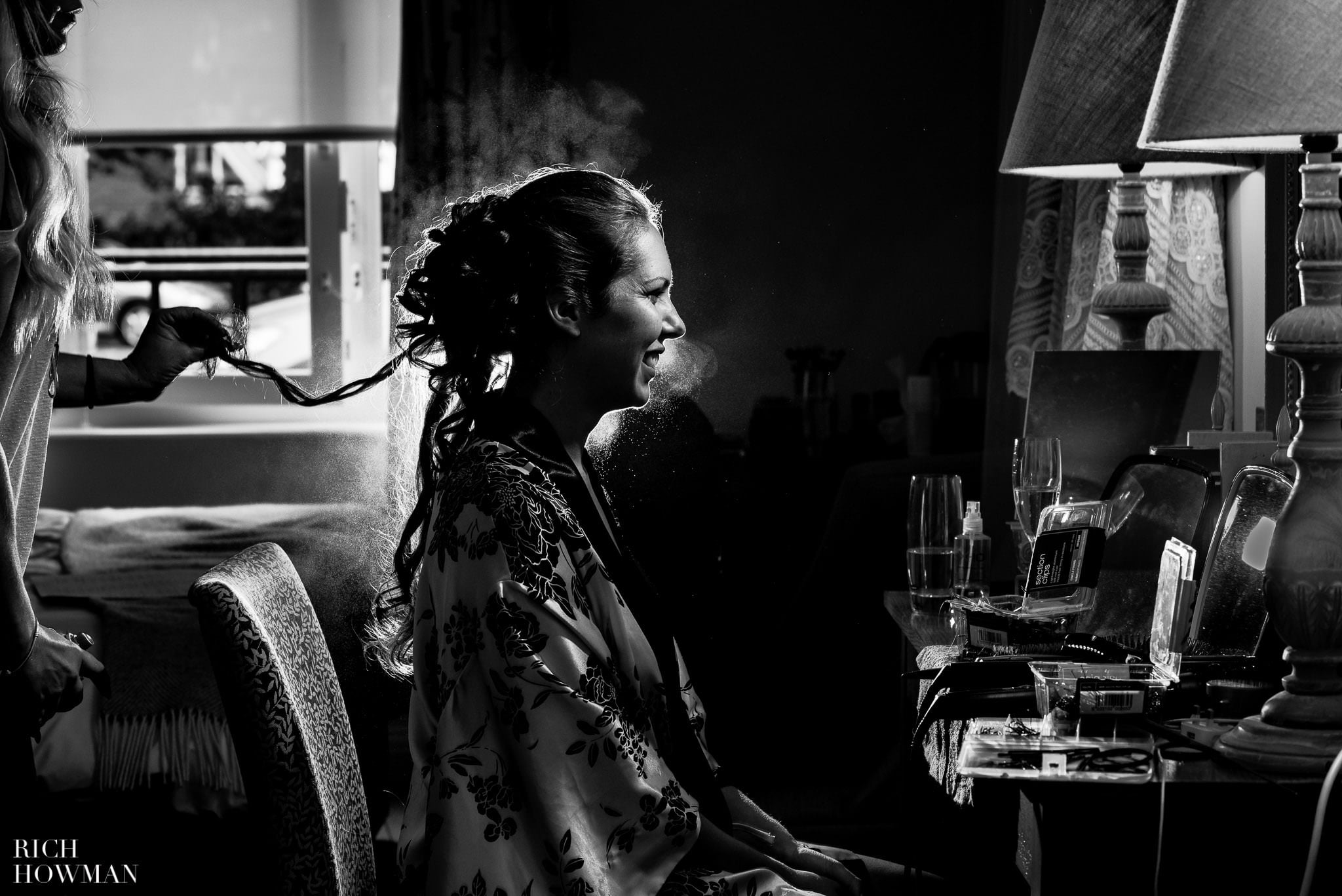backlit black and white photograph of the bride having her hair sprayed at the Coack and Horses in Kew, before her wedding ceremony