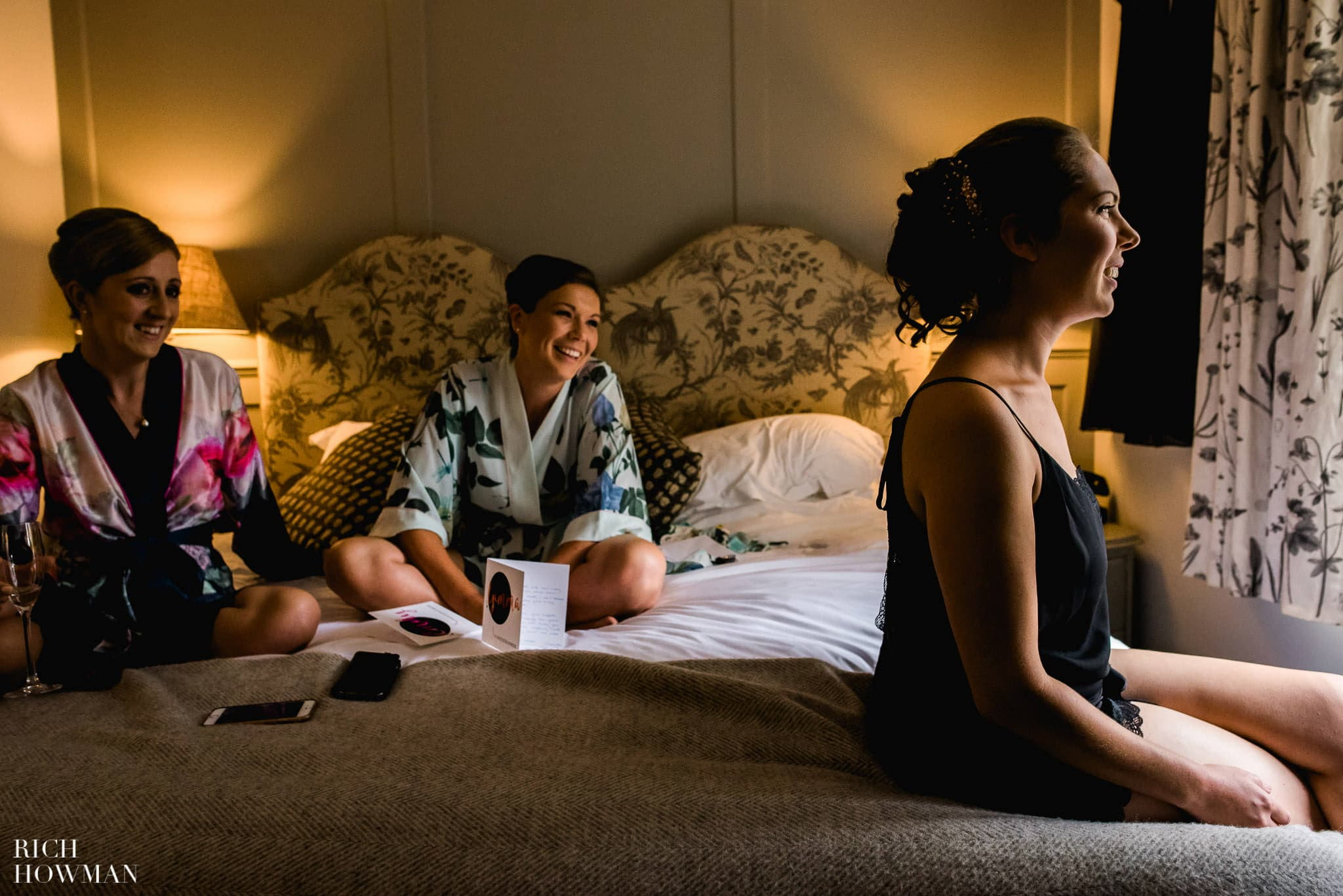Bridesmaids sitting on a bed and sharing laughter with the bride before her wedding at Kew Gardens in London