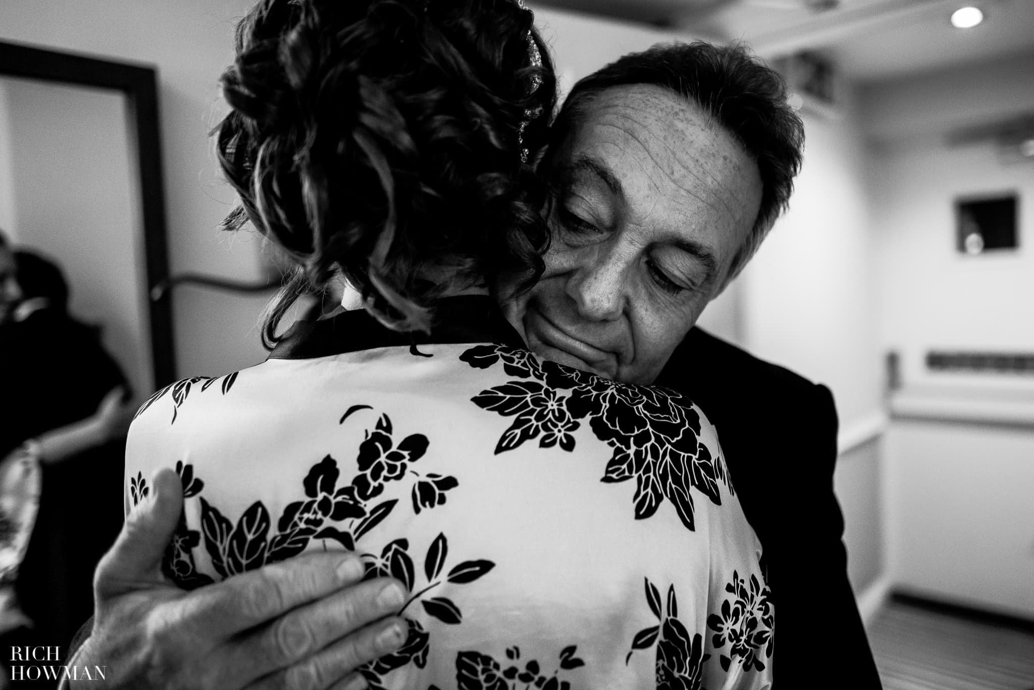 Father of the bride hugs his daughter before walking across Kew Green to her wedding at Kew Gardens, London