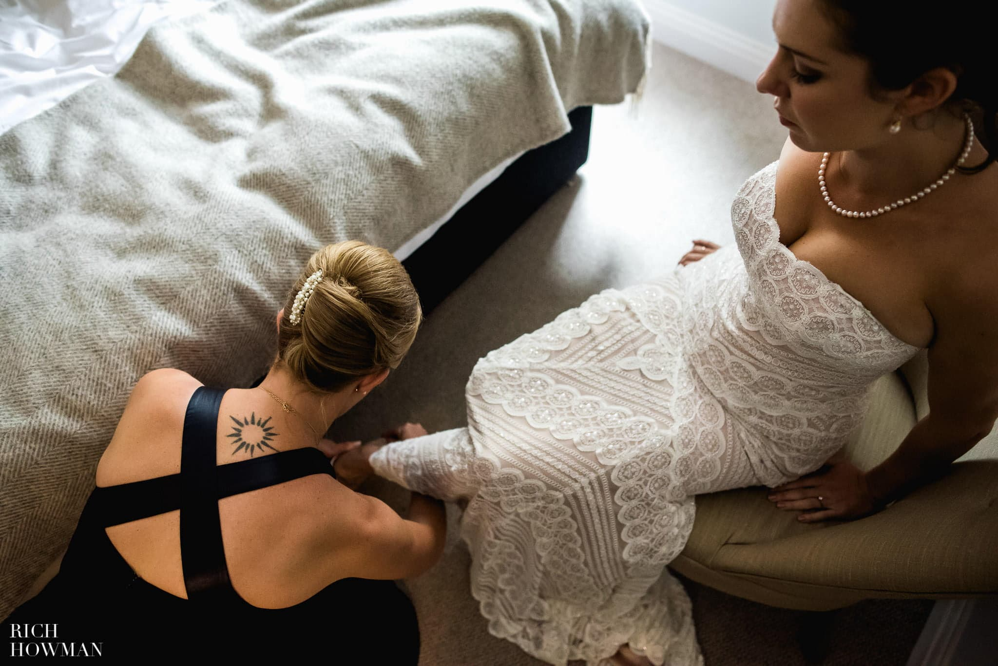 Bridesmaids helps the bride put her shoes on in the morning before her wedding.