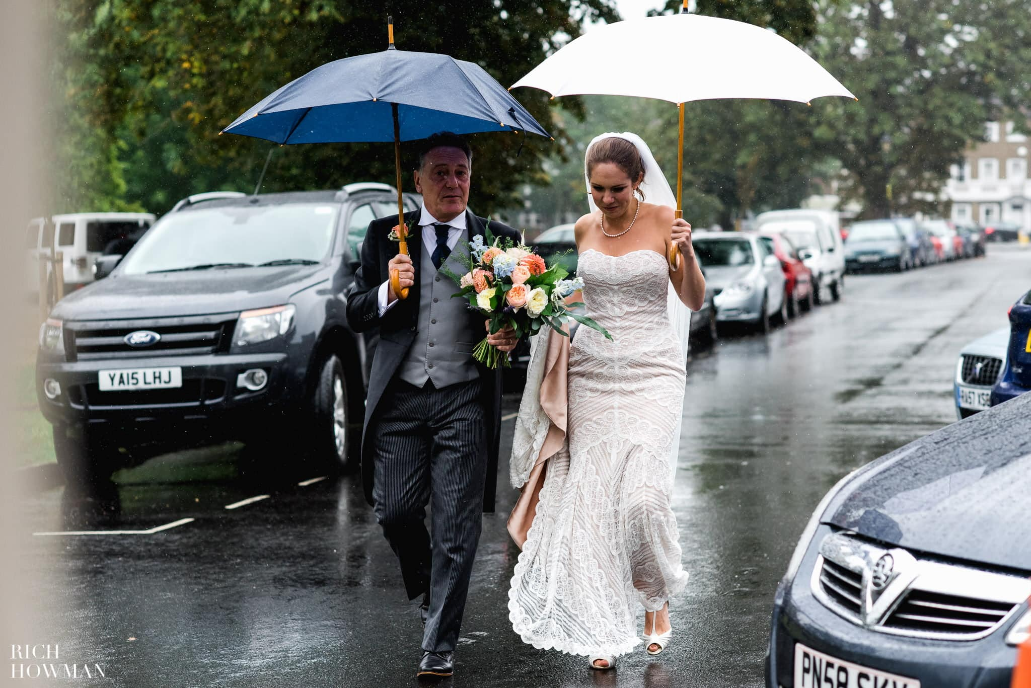 Bride walking across Kew Green with her father to her wedding ceremony at Cambridge Cottage at Kew Gardens